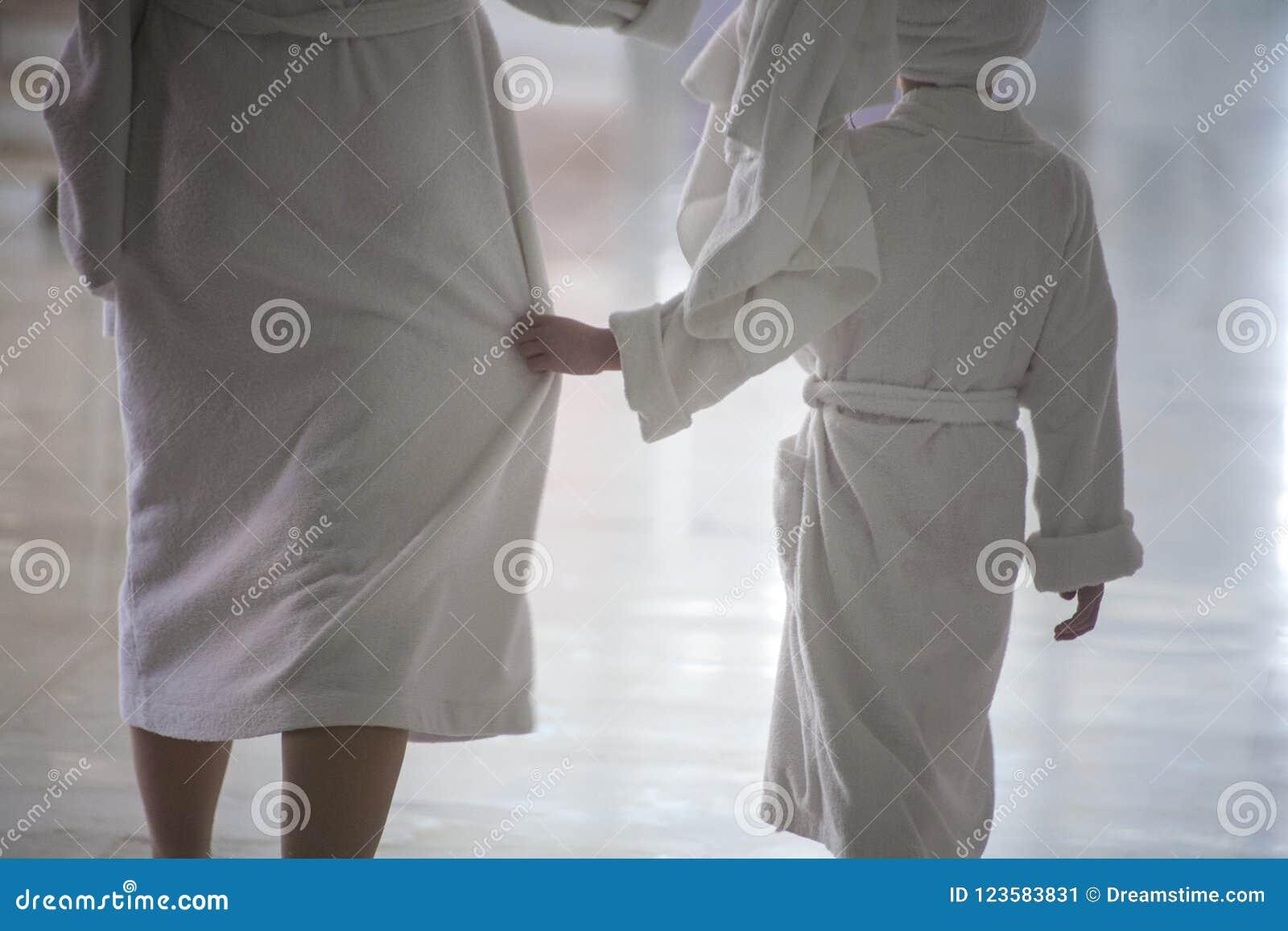 Женщина и ребенок идут в белые купальные халаты