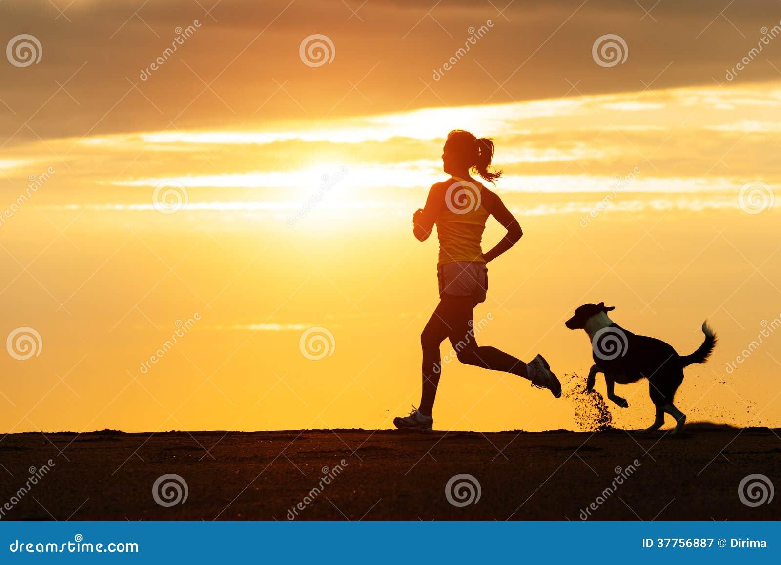 Женщина и собака бежать на пляже на заходе солнца