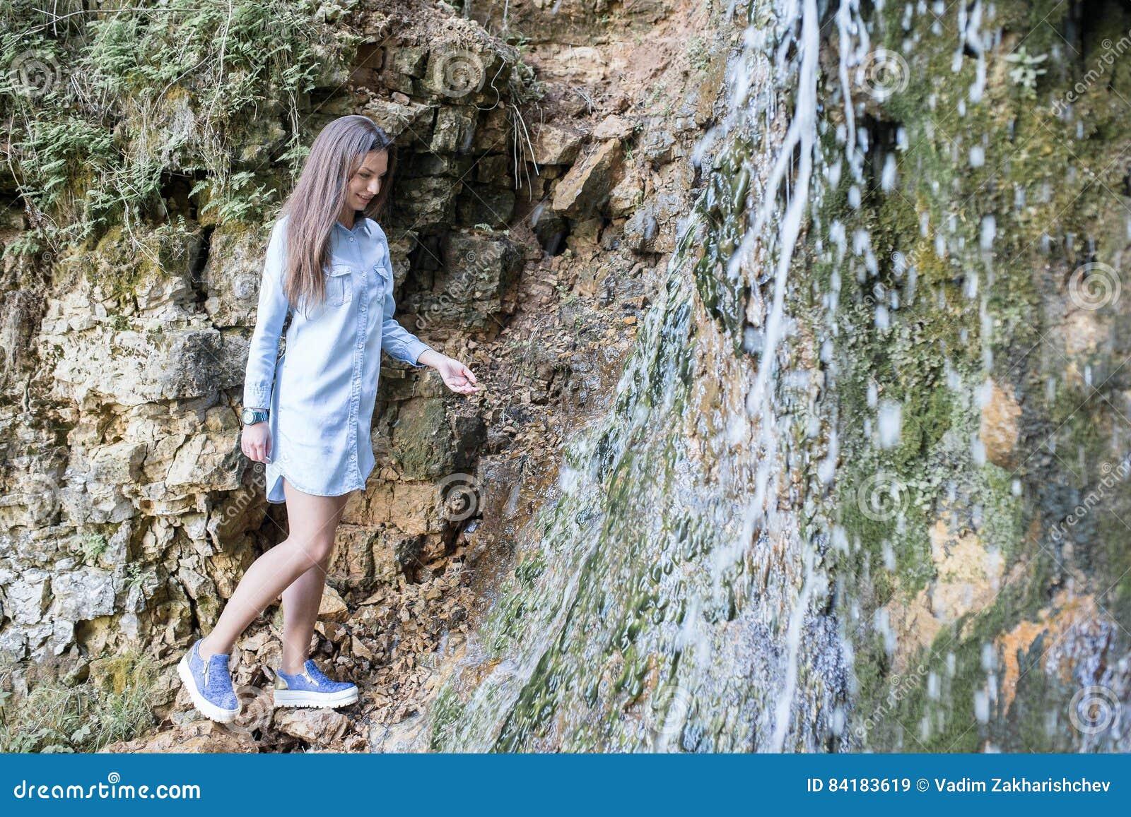 Женщина идя около водопадов горы