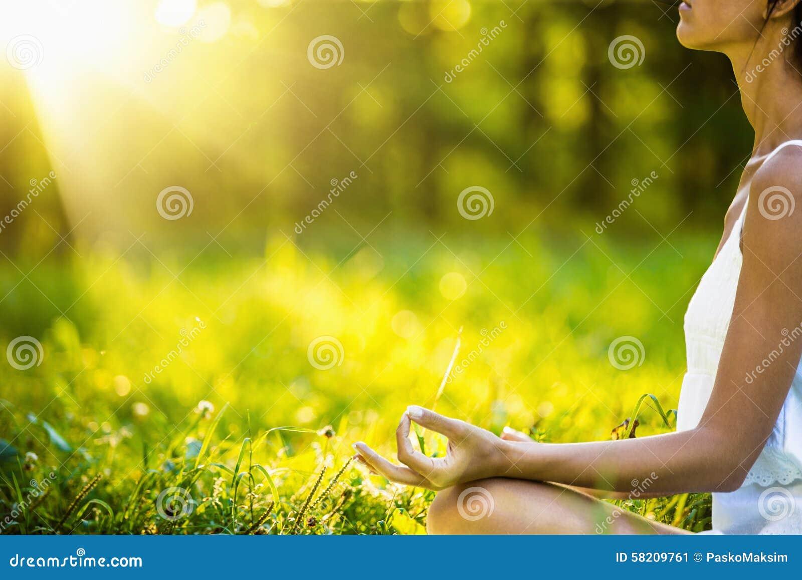 Женщина йоги размышляя на заходе солнца