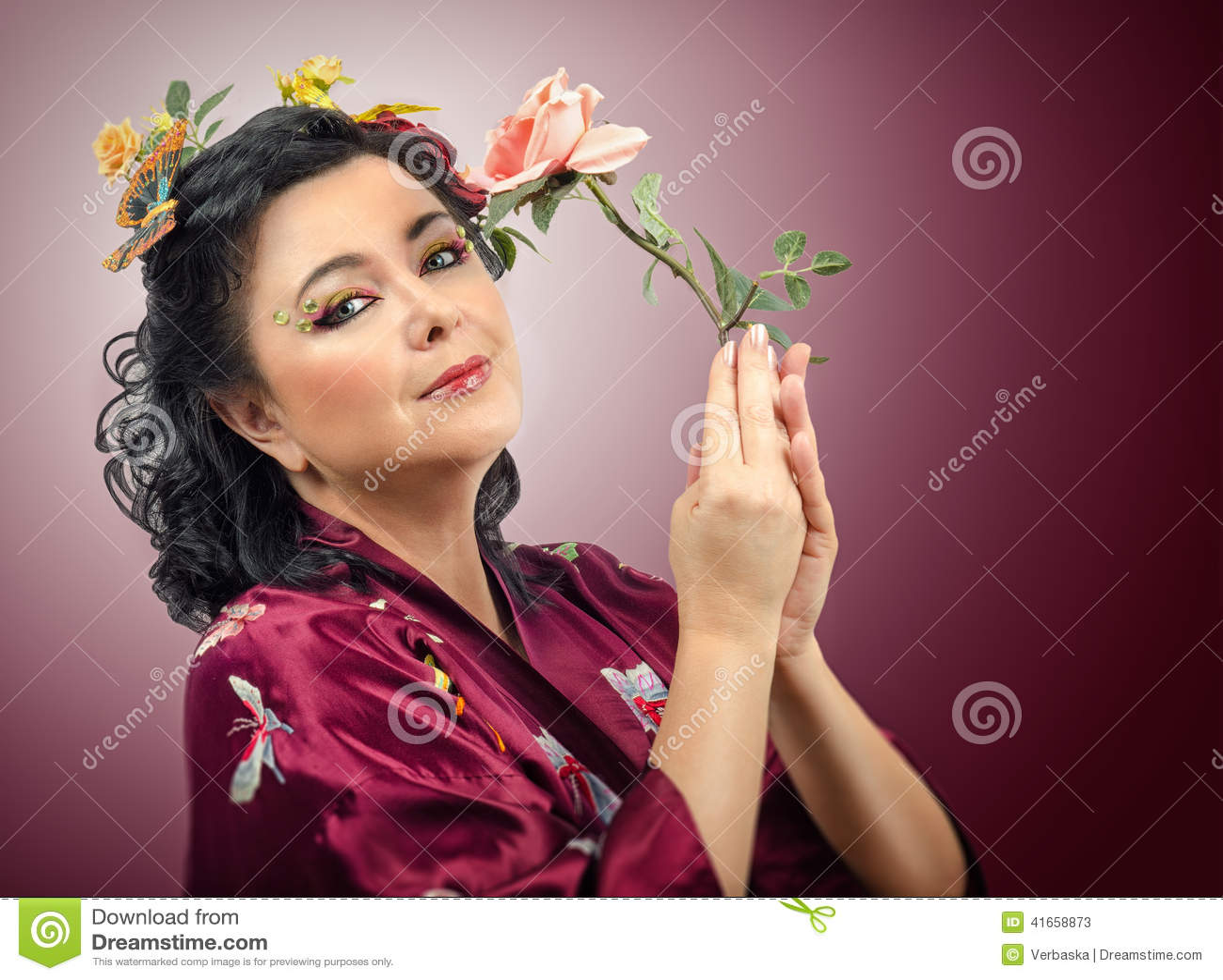 Женщина кимоно кавказская держа розу пинка