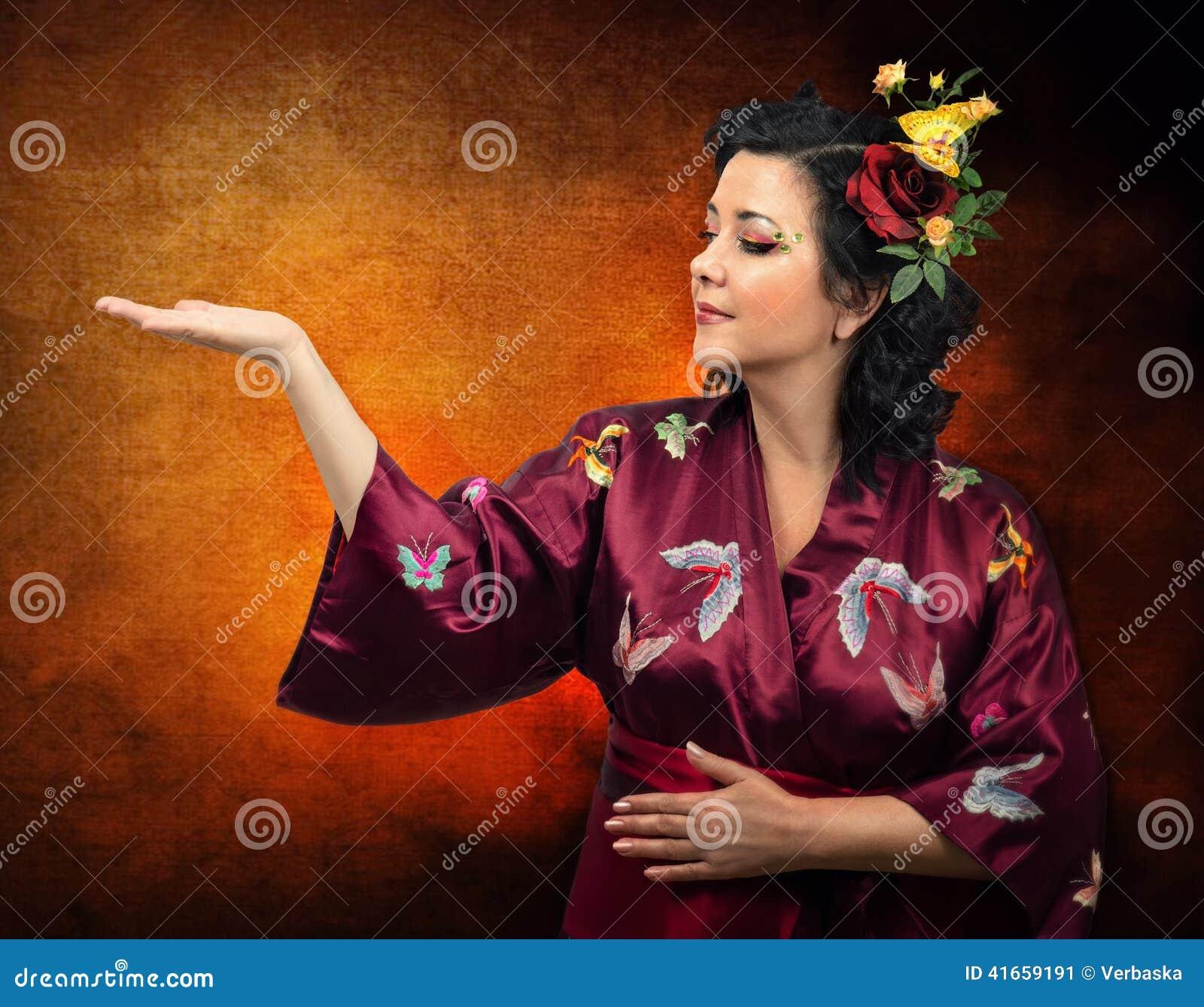 Женщина кимоно кавказская расширяя ее правую руку
