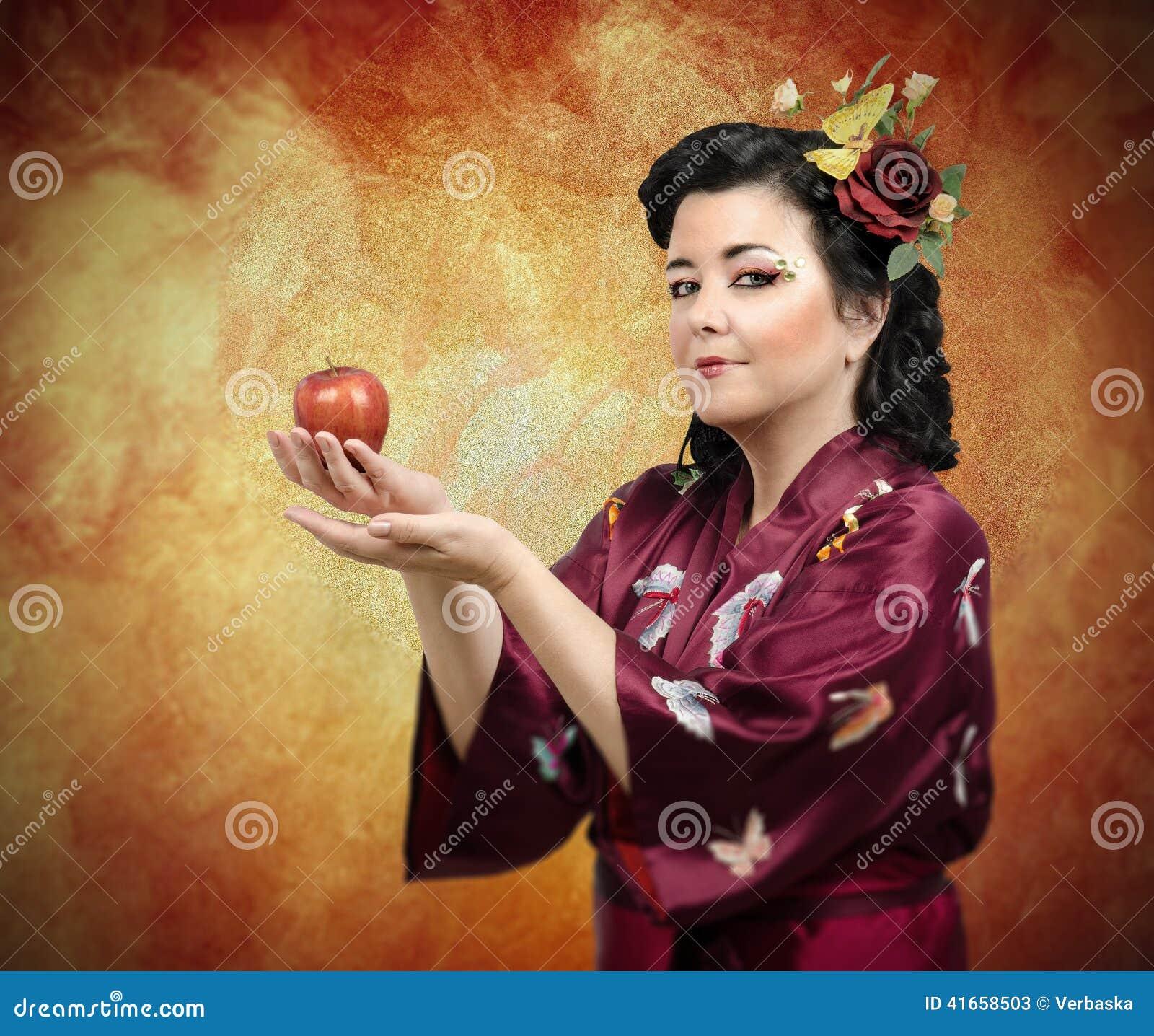Женщина кимоно расширяя ее оружия с яблоком