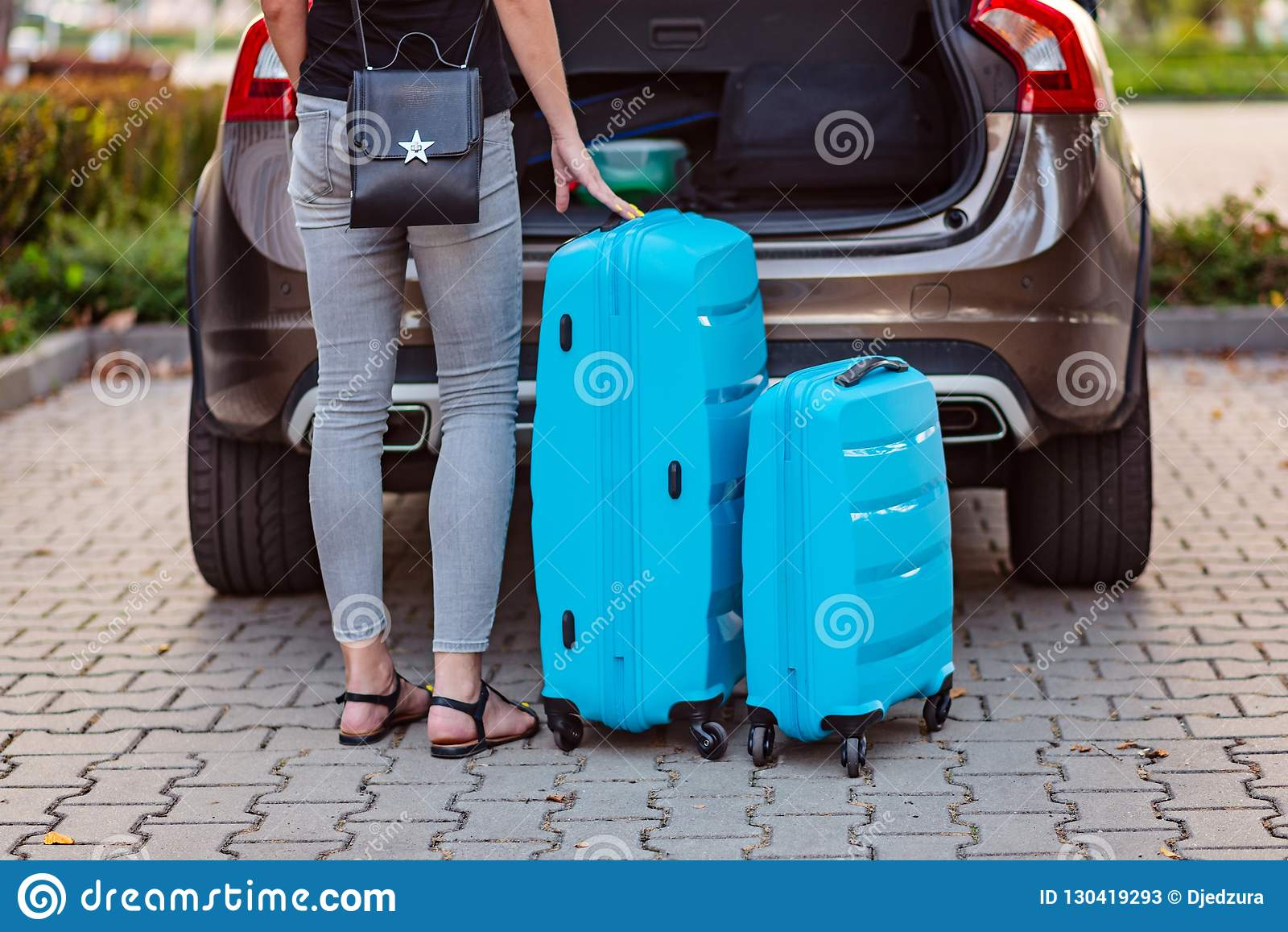 Женщина кладя 2 голубых пластиковых чемодана к багажнику автомобиля