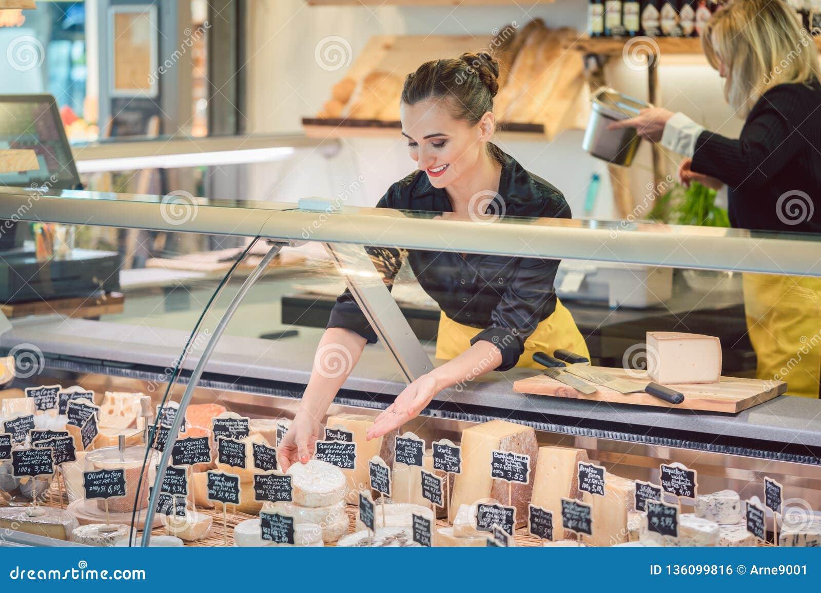 Женщина клерка магазина сортируя сыр в дисплее супермаркета