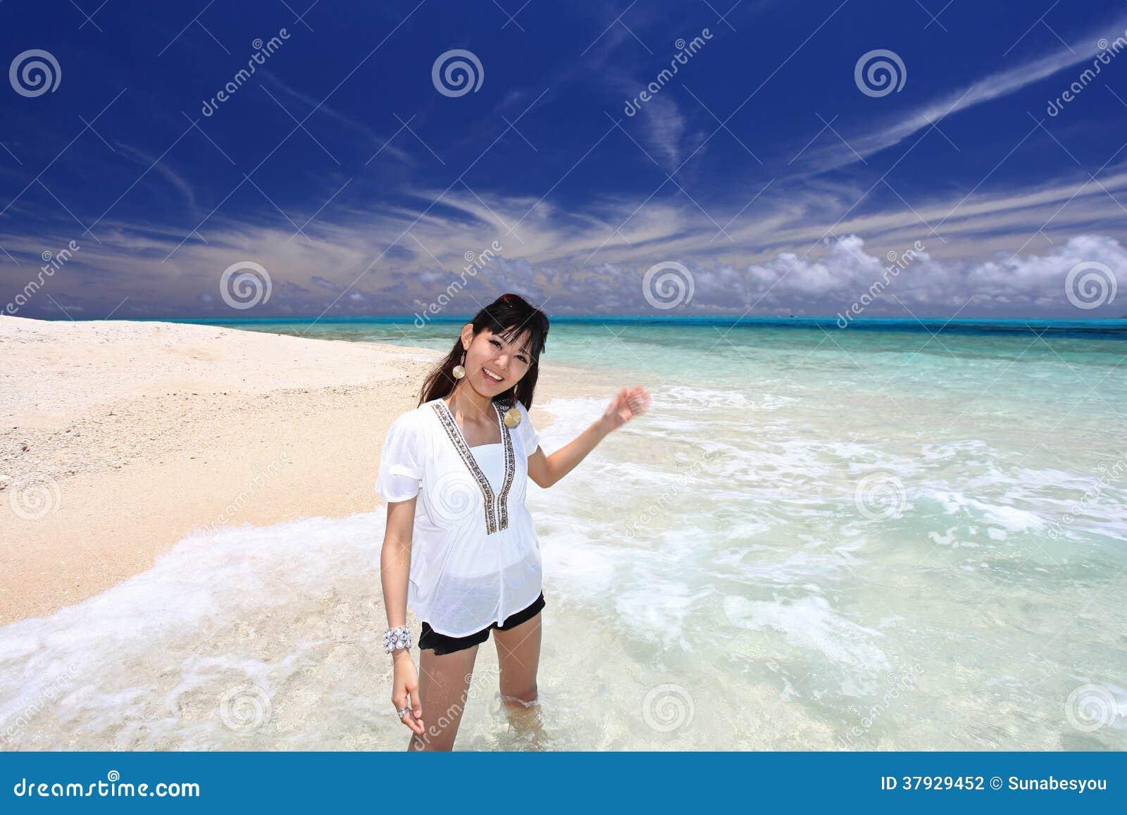 Женщина которая ослабляет на пляже.