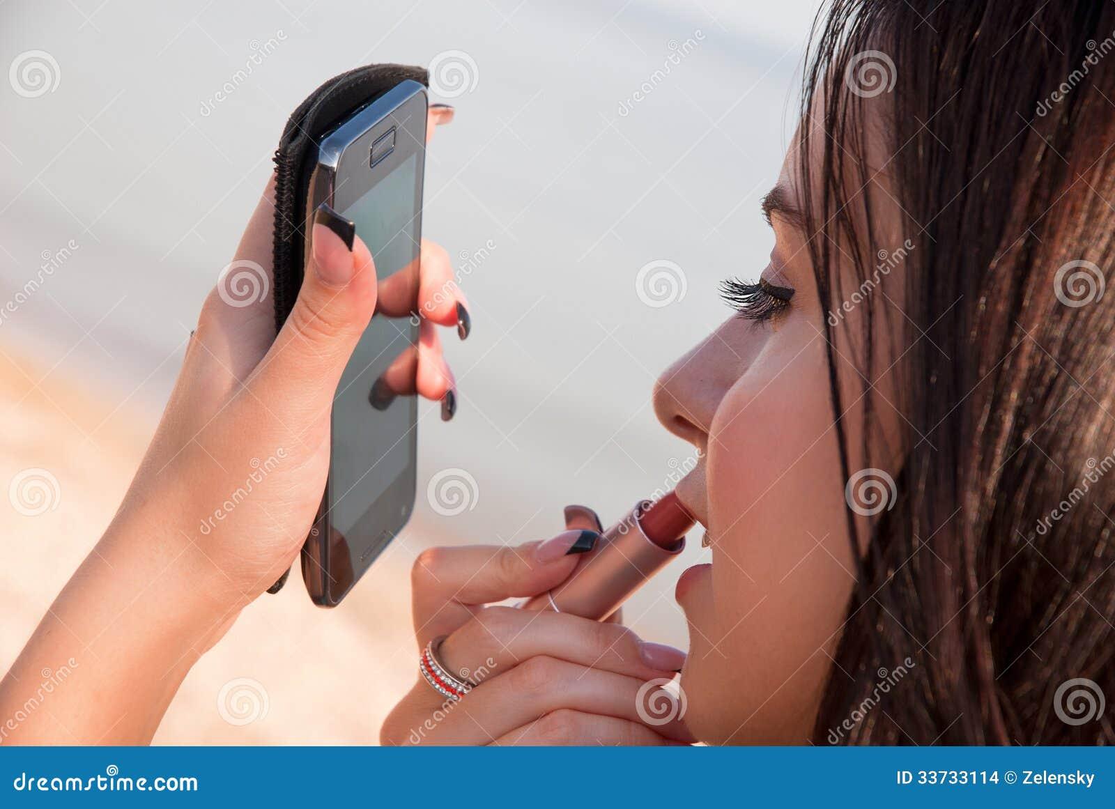 Женщина красит ее губы