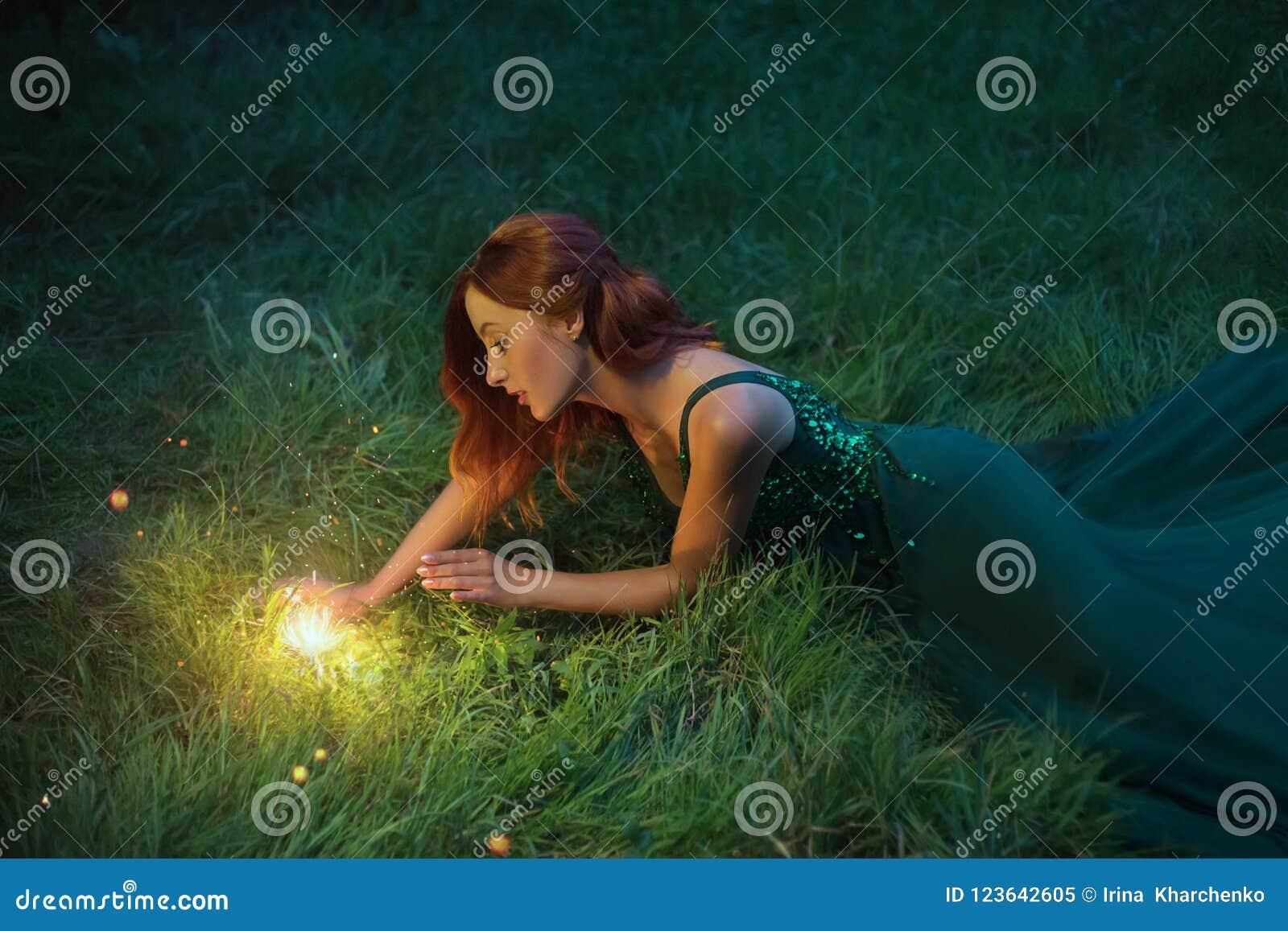 Женщина красных волос очаровательная лежит на траве в чудесном изумрудном платье с длинным поездом