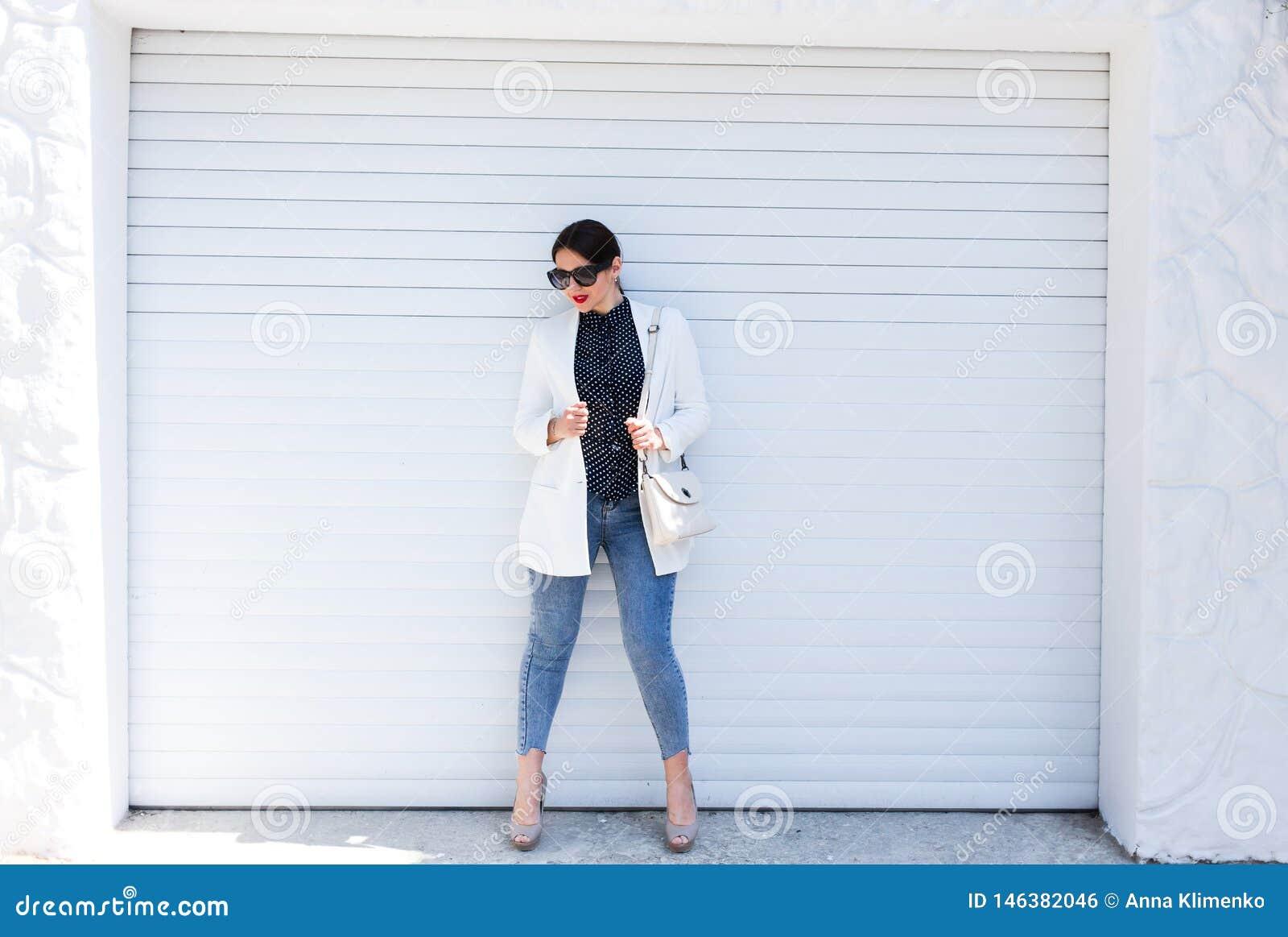 Женщина милой молодой моды чувственная представляя на белой предпосылке стены одетой в обмундировании джинсов стиля и белой куртк