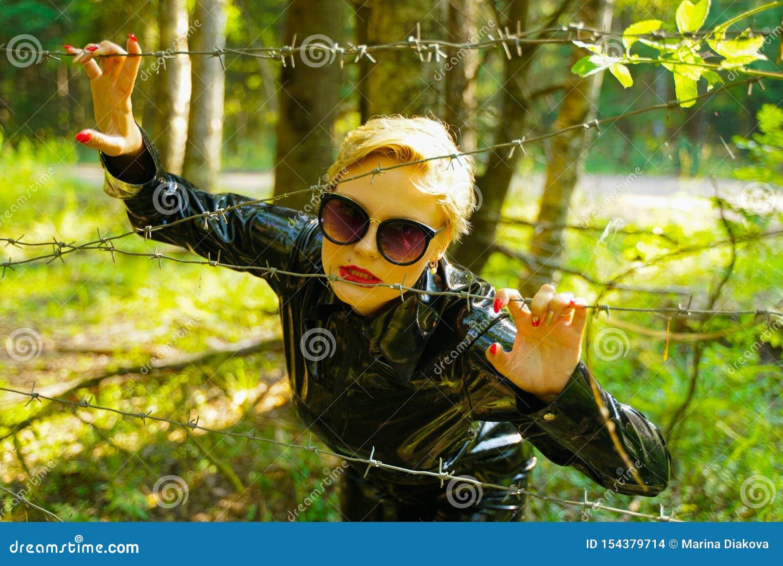 Женщина моды латекса резиновая идя в лес