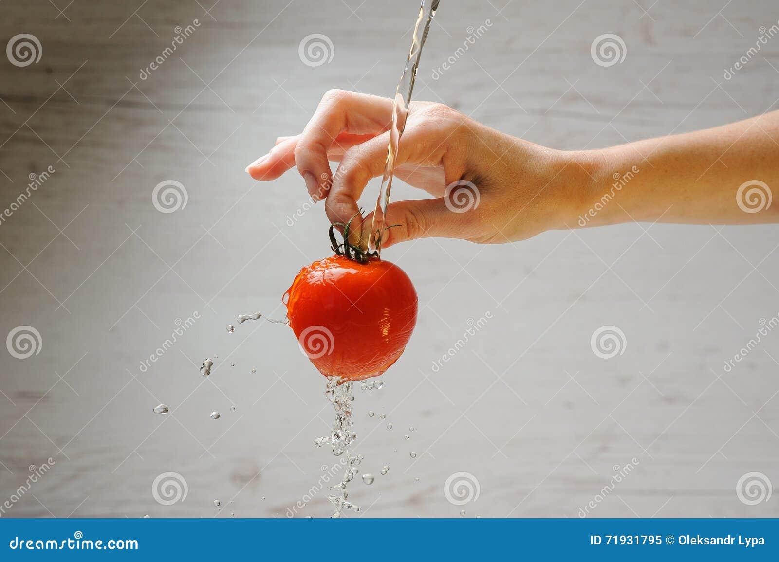 Женщина моет томат