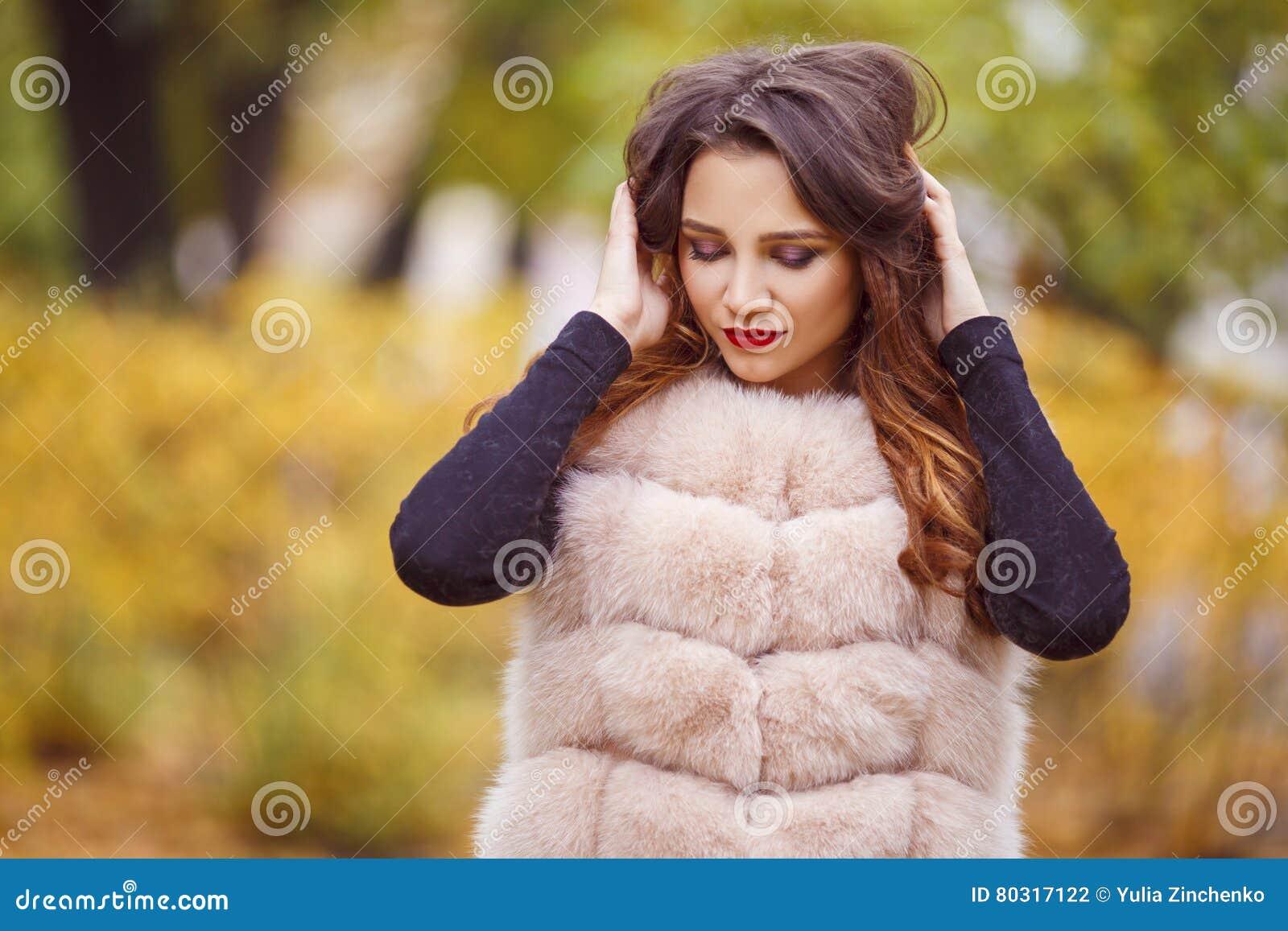 Женщина моды красоты в жилете меха идет в парк Осень