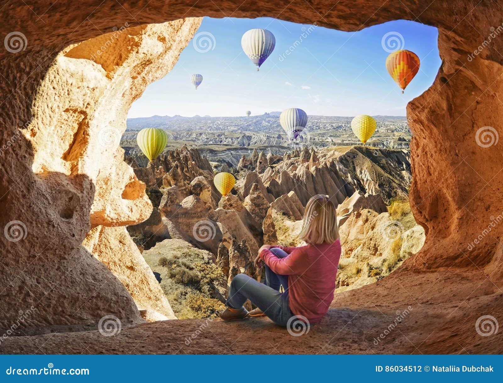 Женщина наблюдая как красочные горячие воздушные шары летая над долиной на Cappadocia
