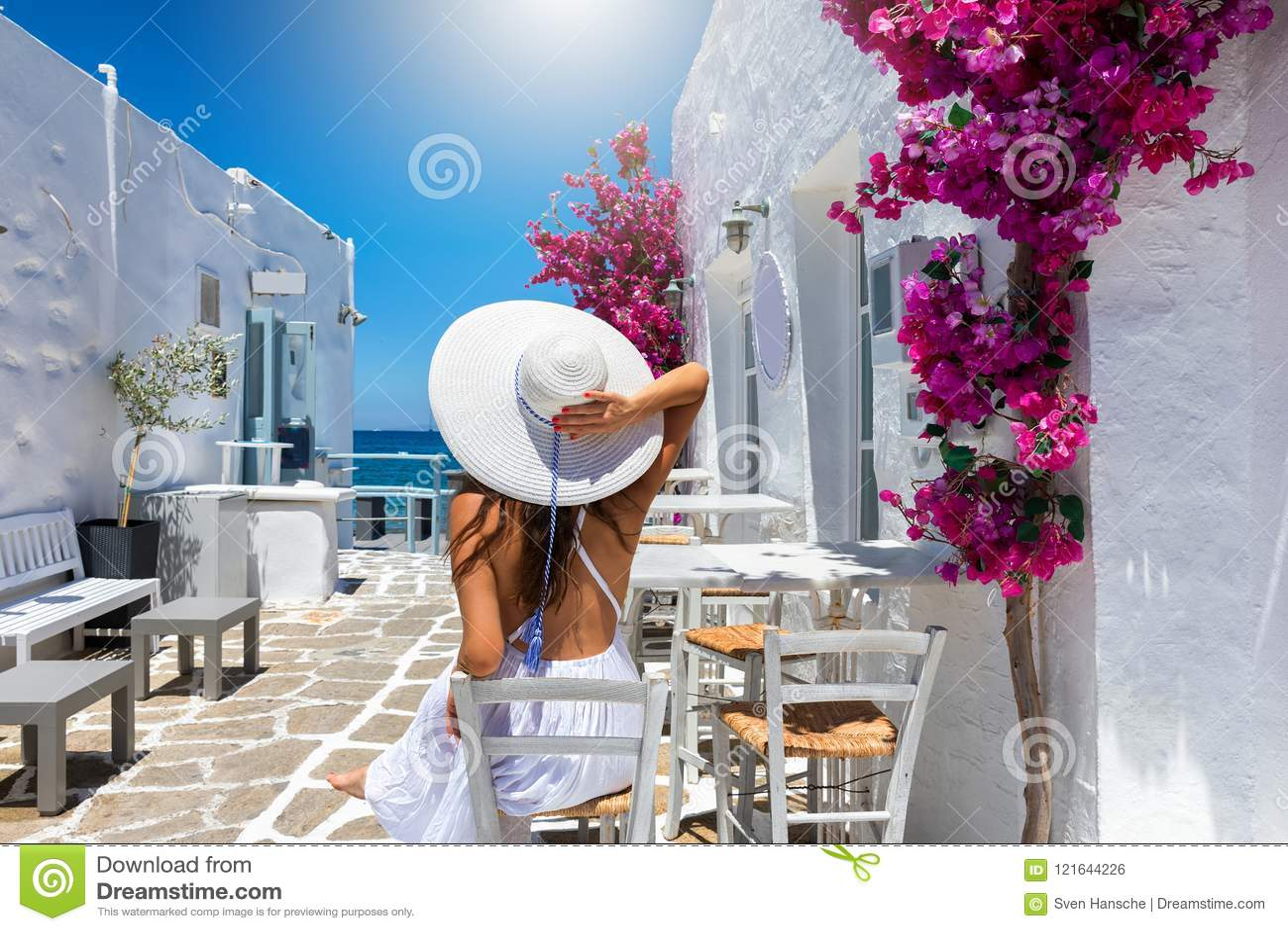 Женщина наслаждается классической установкой Белых Домов и красочных цветков на островах Кикладов Греции
