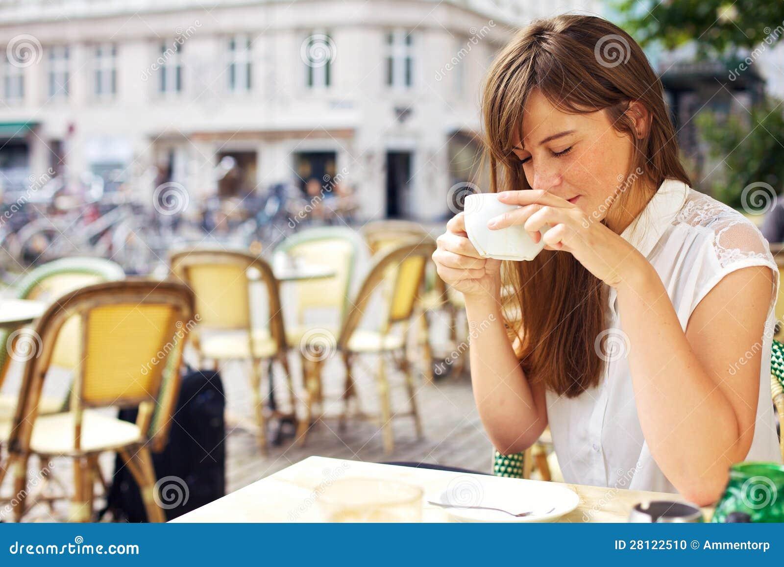 Женщина наслаждаясь ароматностью ее кофе