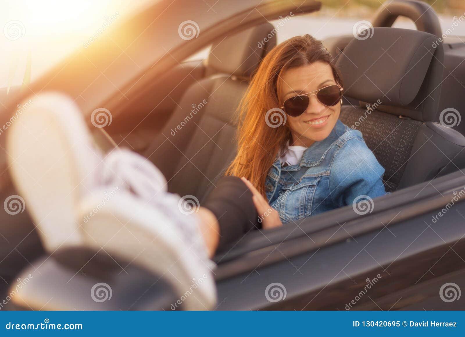 Женщина наслаждаясь обратимым автомобилем на заходе солнца