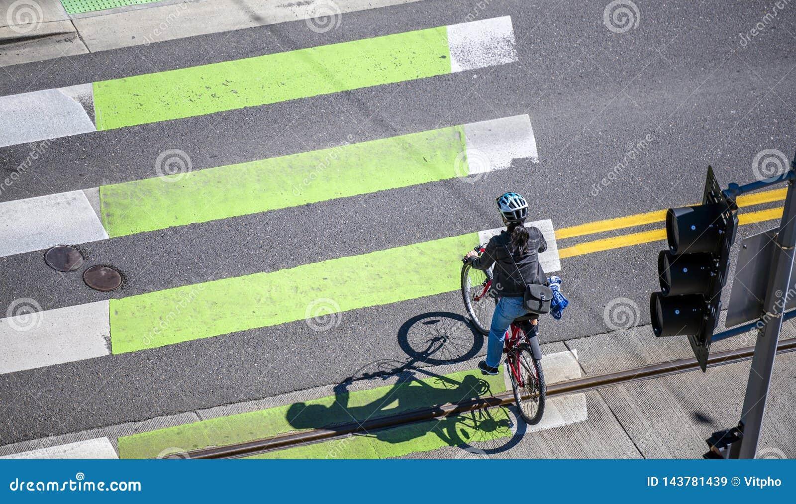 Женщина на велосипеде пересекает дорогу на пешеходный переход