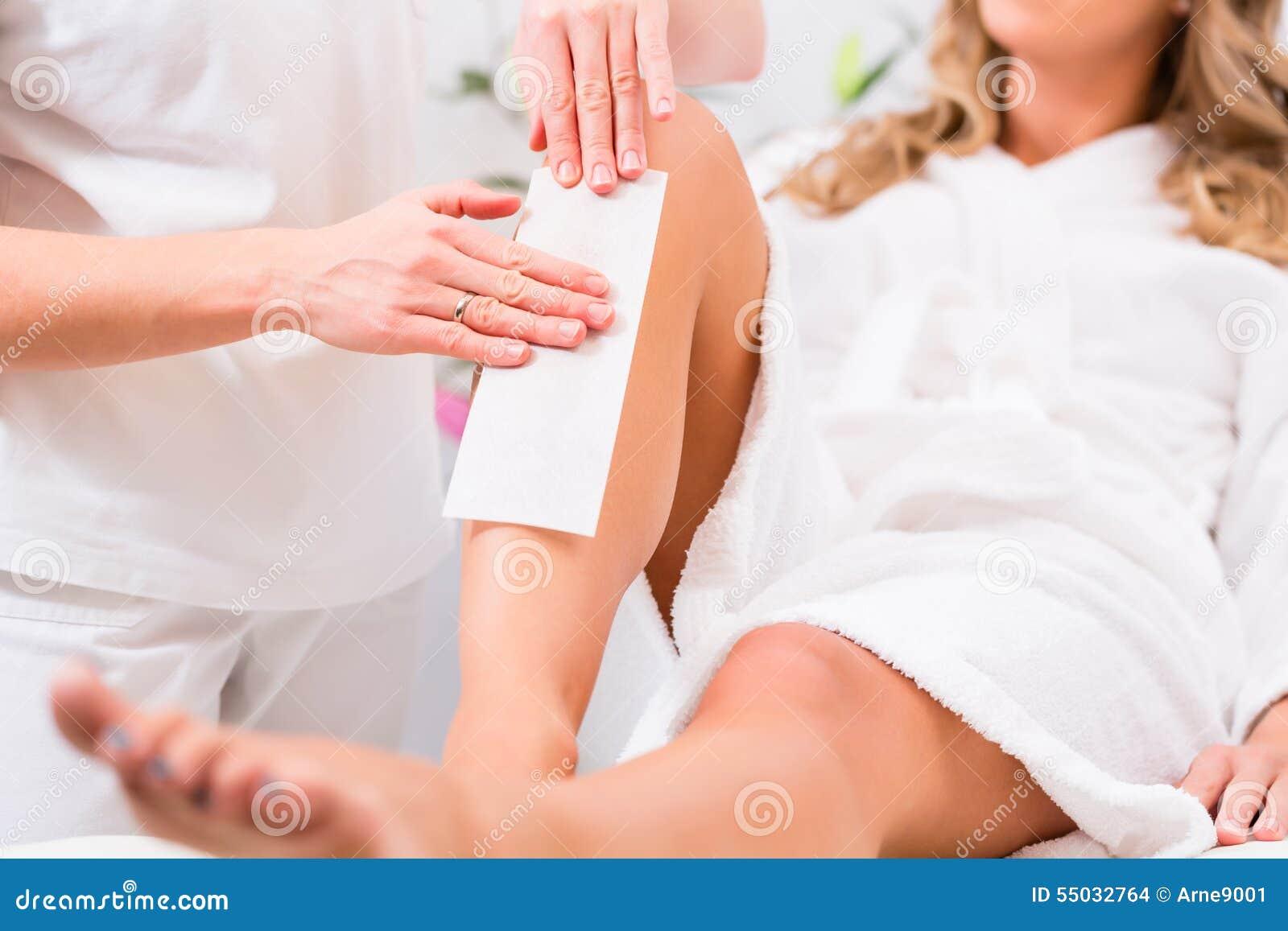 Женщина на вощить удаление волос в косметическом кабинете