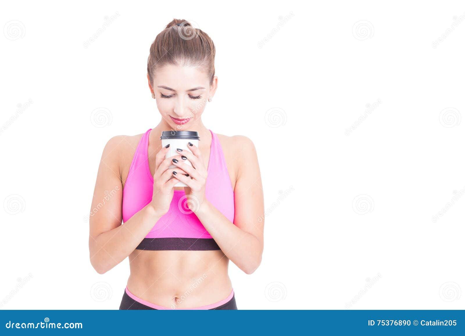 Женщина на спортзале держа кофейную чашку на проломе