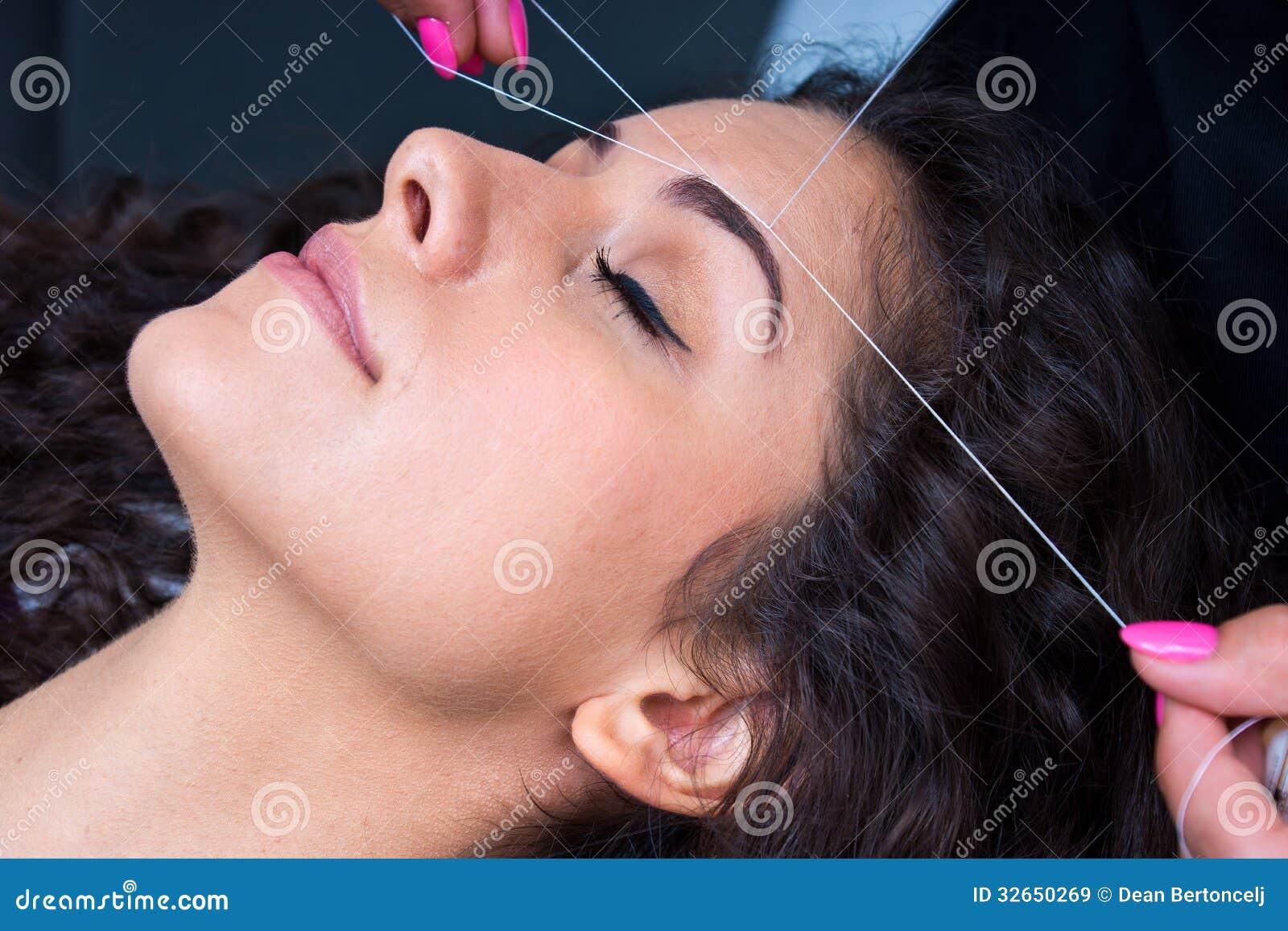 Женщина на удалении волос на лице продевая нитку процедуру