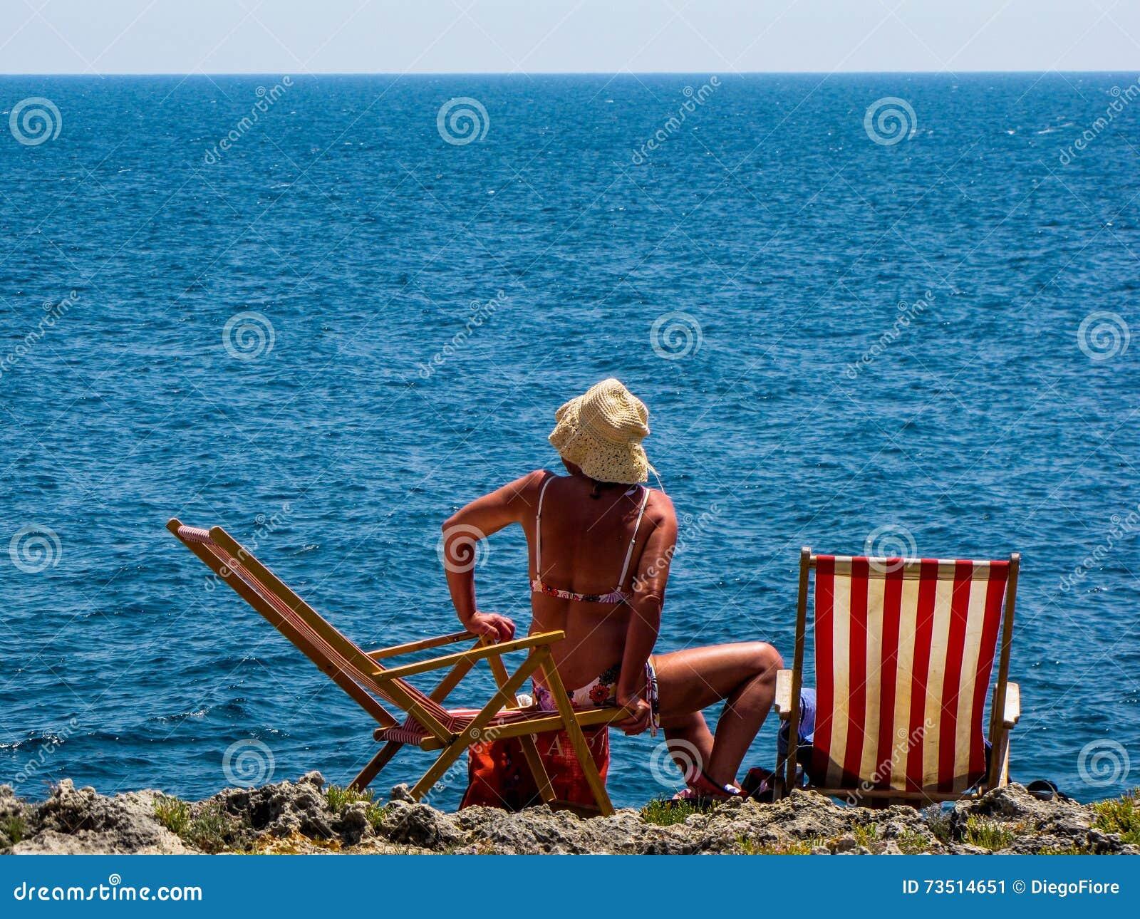 Женщина на deckchair морем