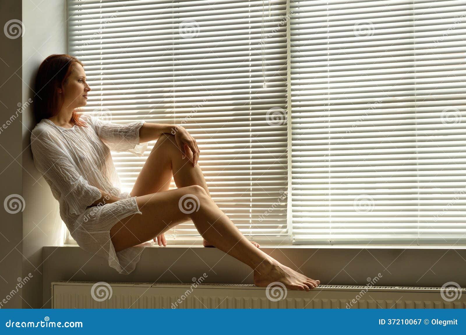 Женщина на windowsill дома