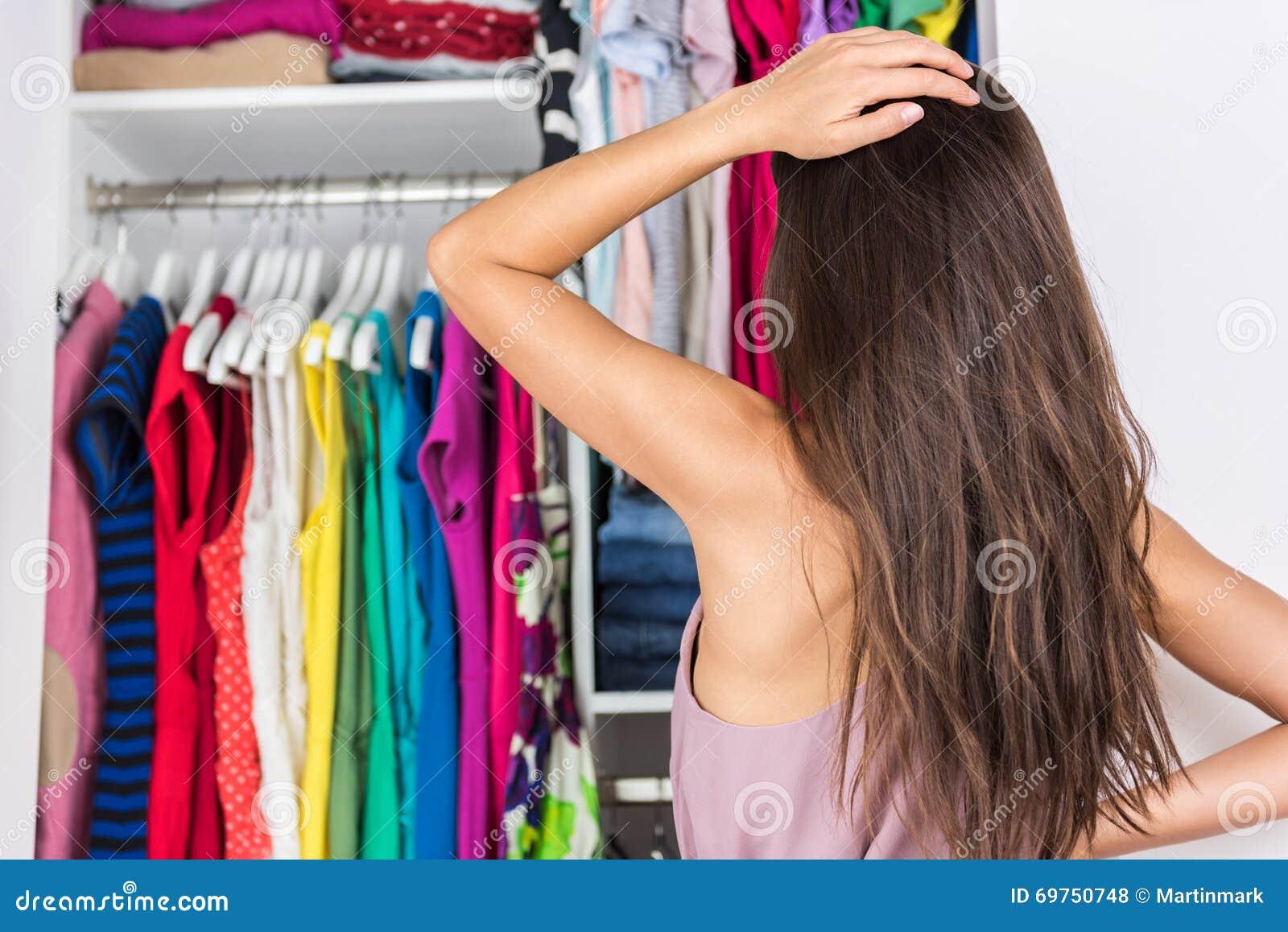 Женщина нерешительности выбирая обмундирование в шкафе одежд