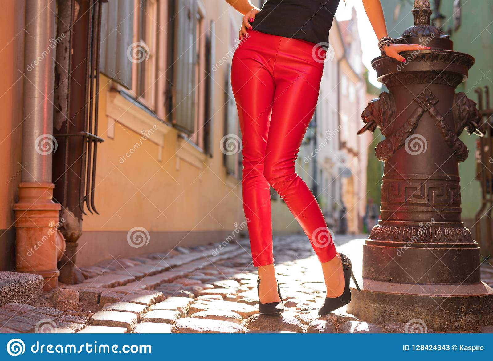 Женщина нося яркие красные кожаные брюки и высокие пятки