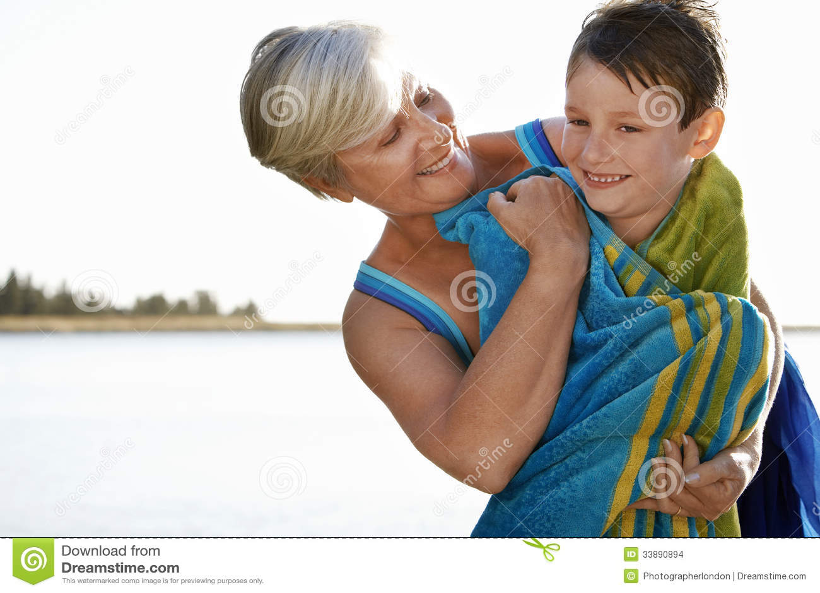 Женщина обнимая внука обернутого в полотенце