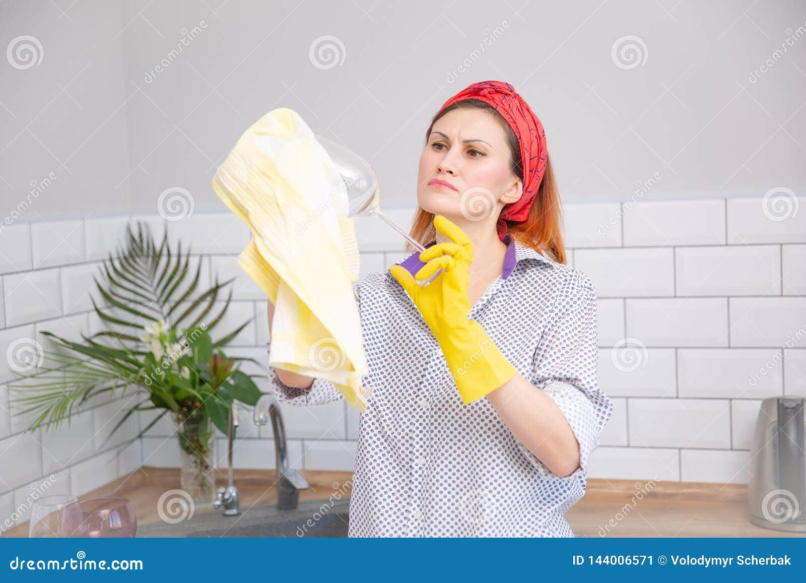 Женщина обтирая стекло с полотенцем в кухне