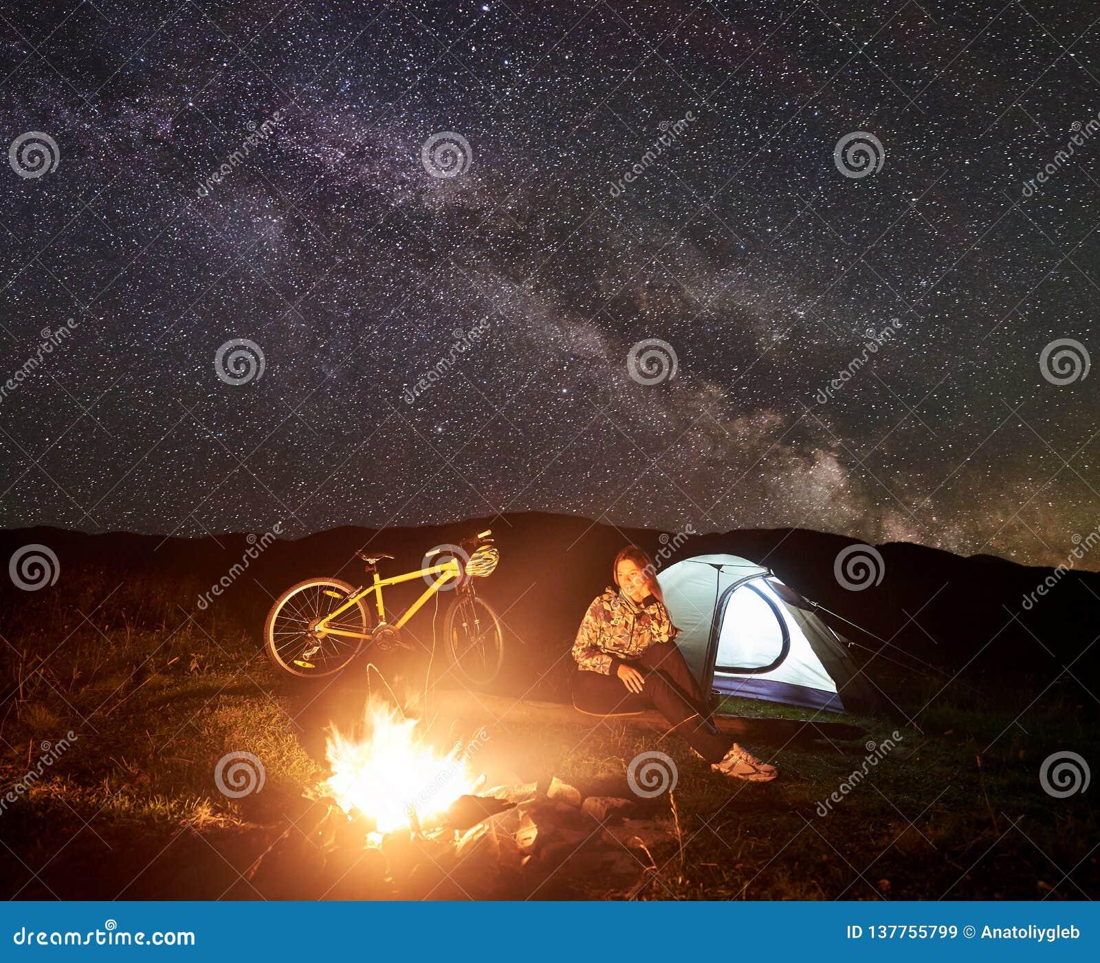 Женщина отдыхая на ноче располагаясь лагерем около лагерного костера, туристского шатра, велосипеда под небом вечера вполне звезд