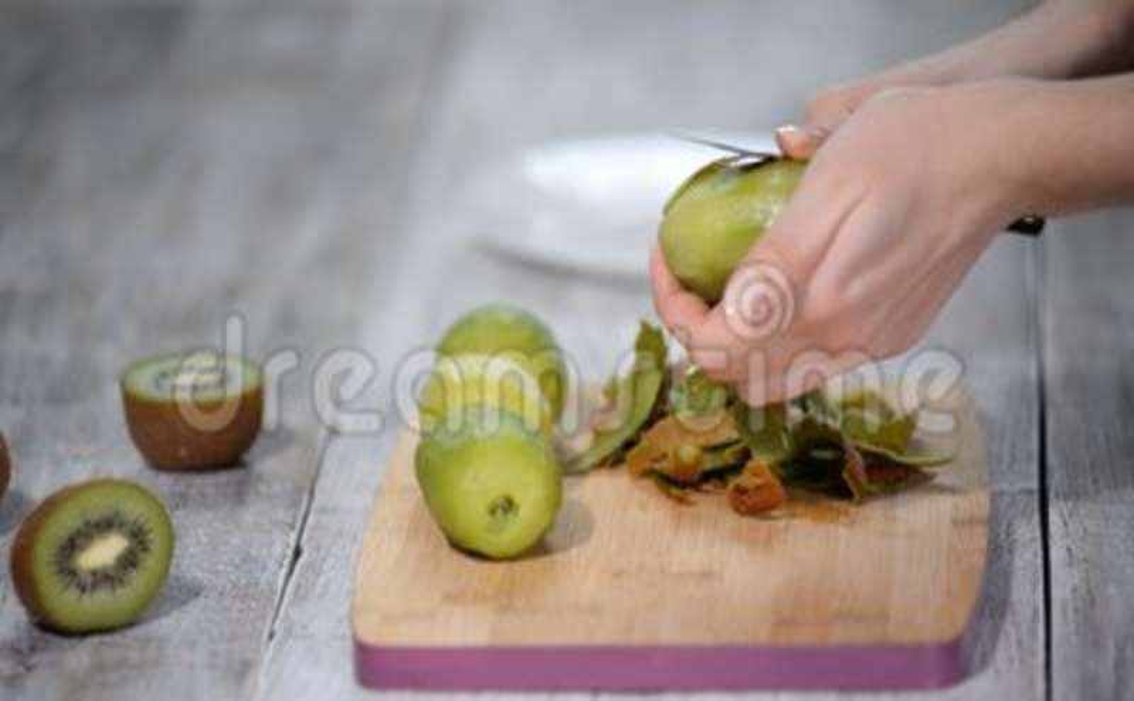 Женщина очищает корку кивиа с ножом на деревянной предпосылке сток-видео