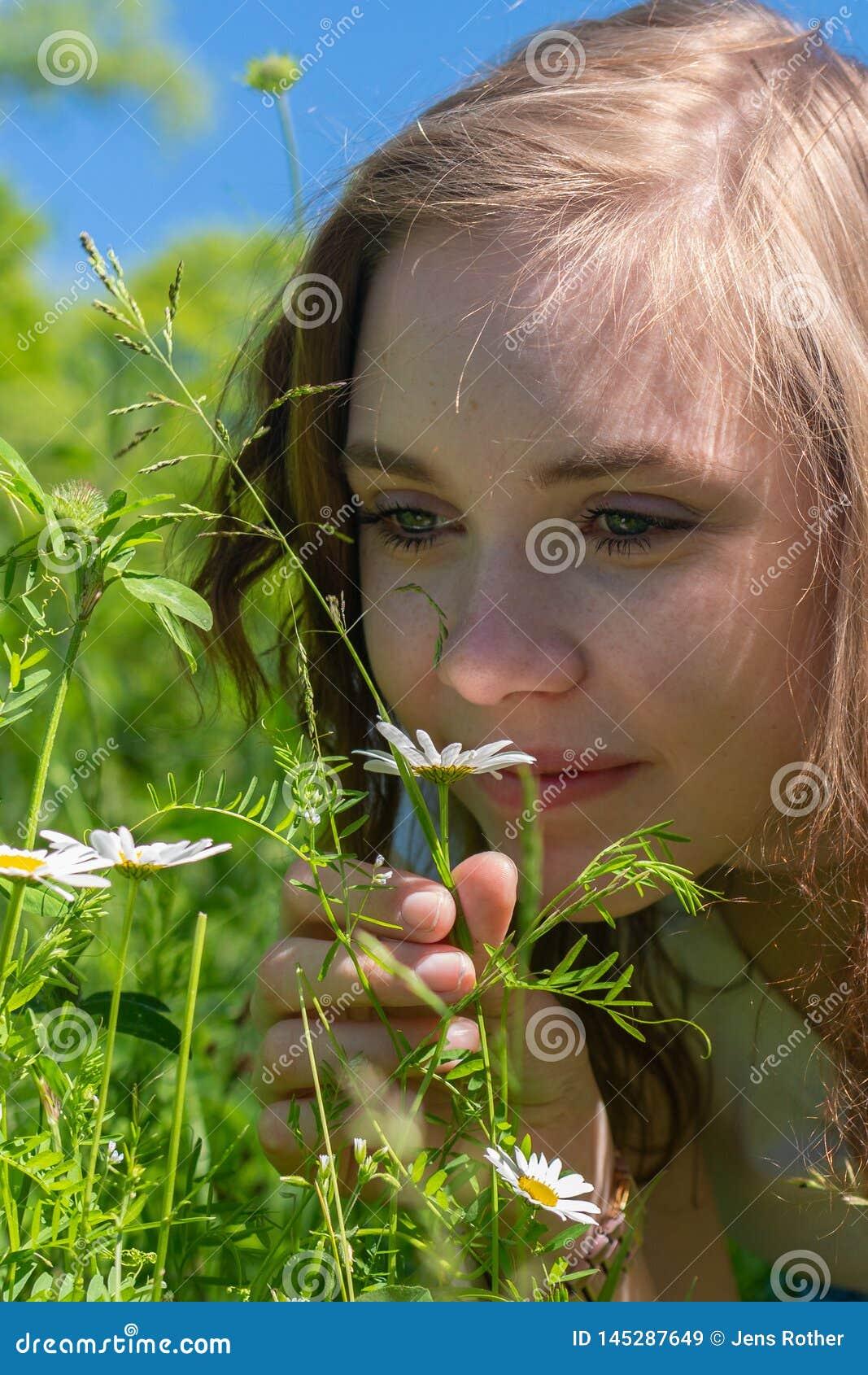 Женщина пахнет на цветках в парке