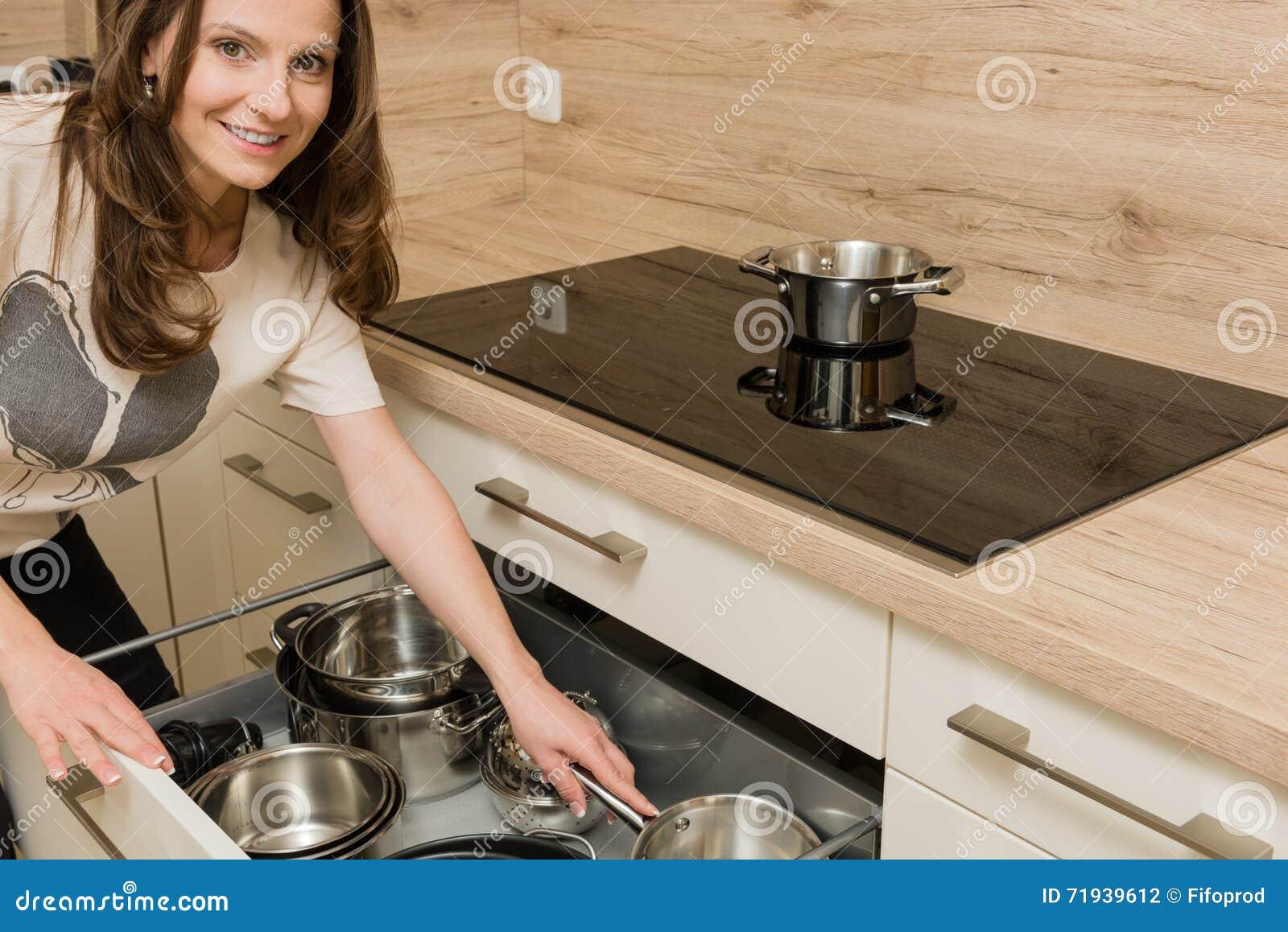 Женщина перед современным плитаом с открытым ящиком под плитой