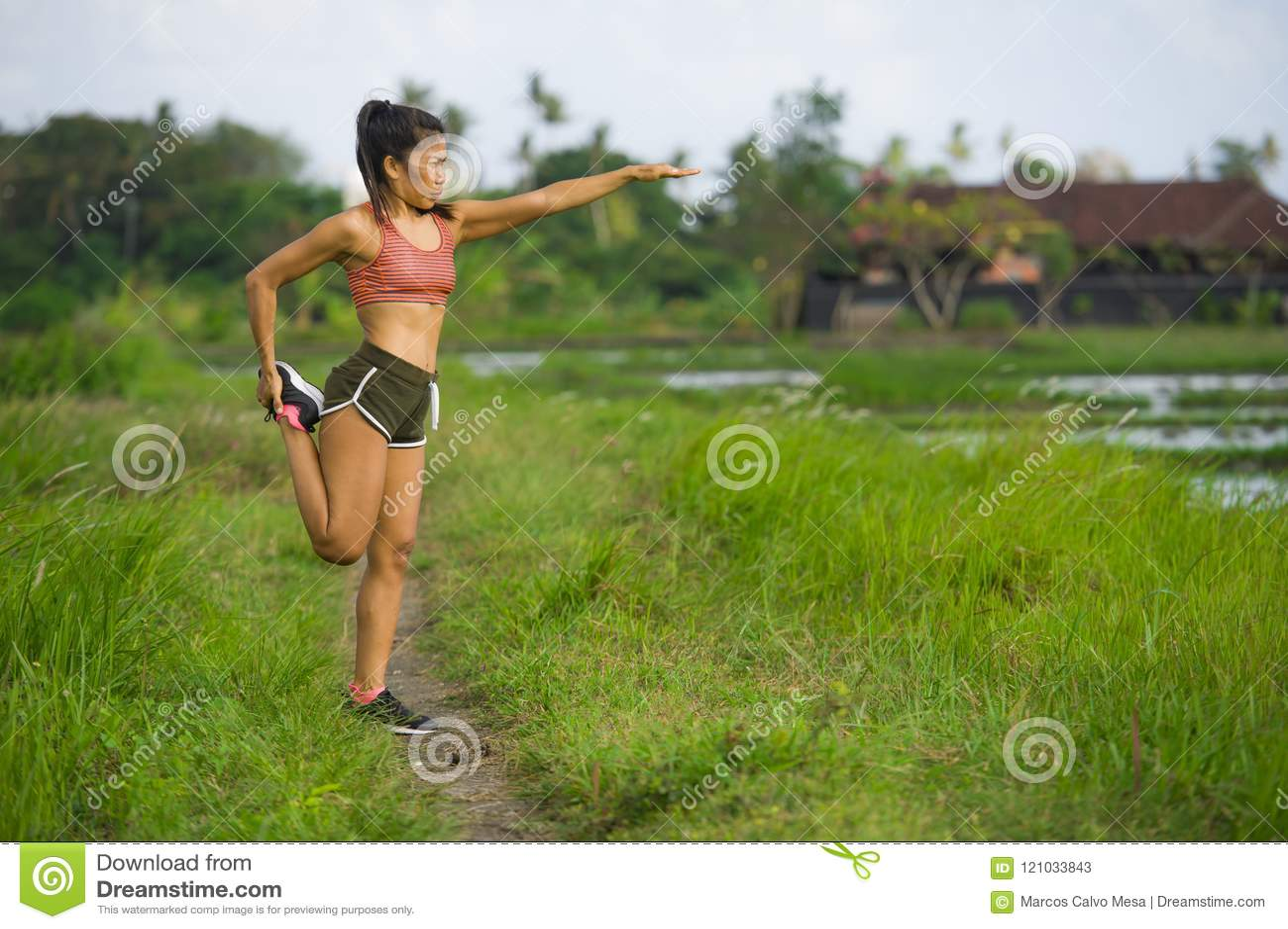 Женщина подходящего и sporty бегуна азиатская протягивая ногу и тело после идущей разминки на предпосылке зеленого поля красивой