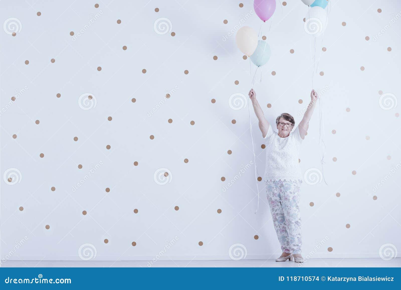 Женщина позитва усмехаясь пожилая с красочными воздушными шарами против wh