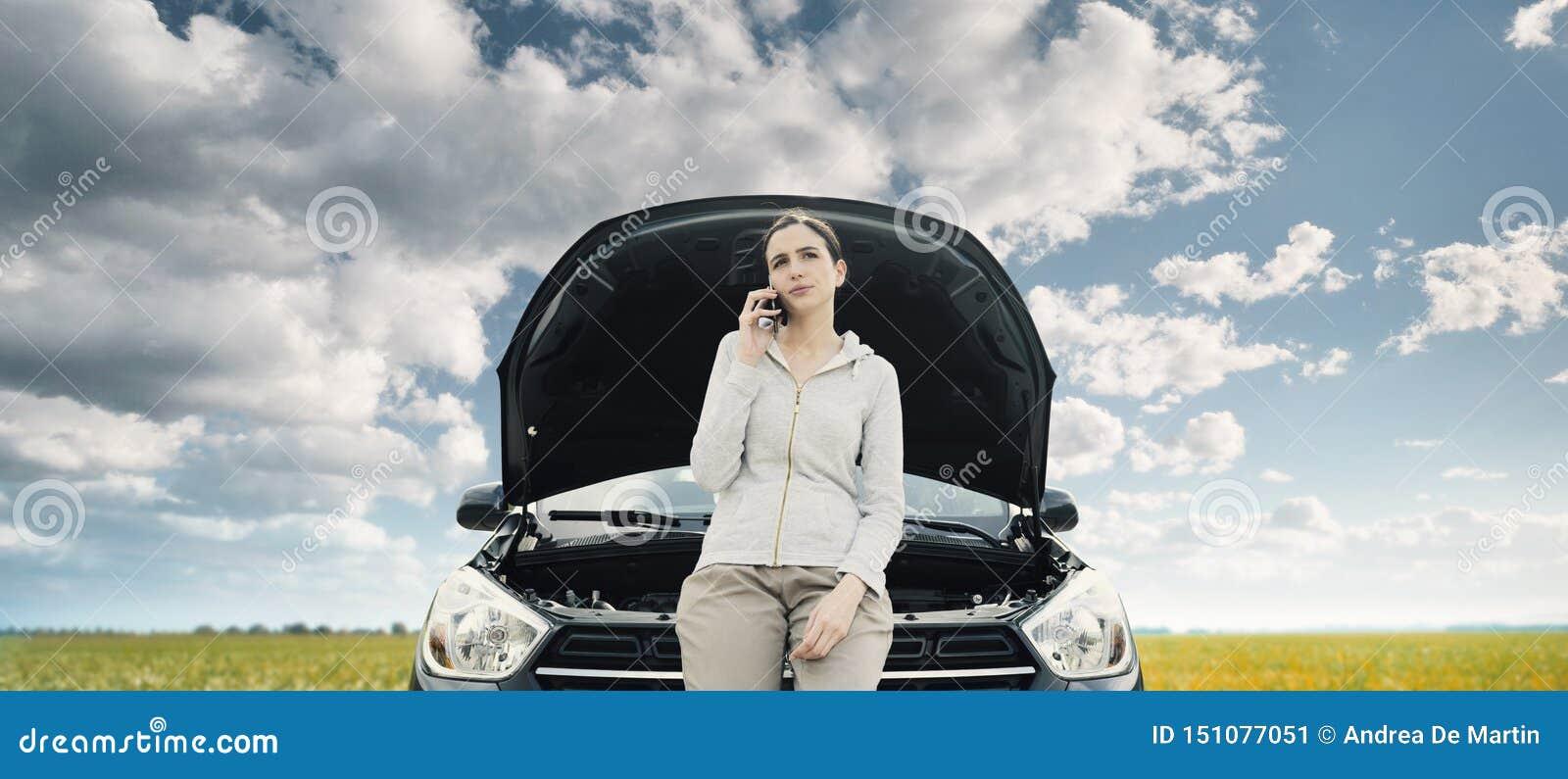 Женщина полагаясь на автомобиле и вызывая ремонтные услуги автомобиля