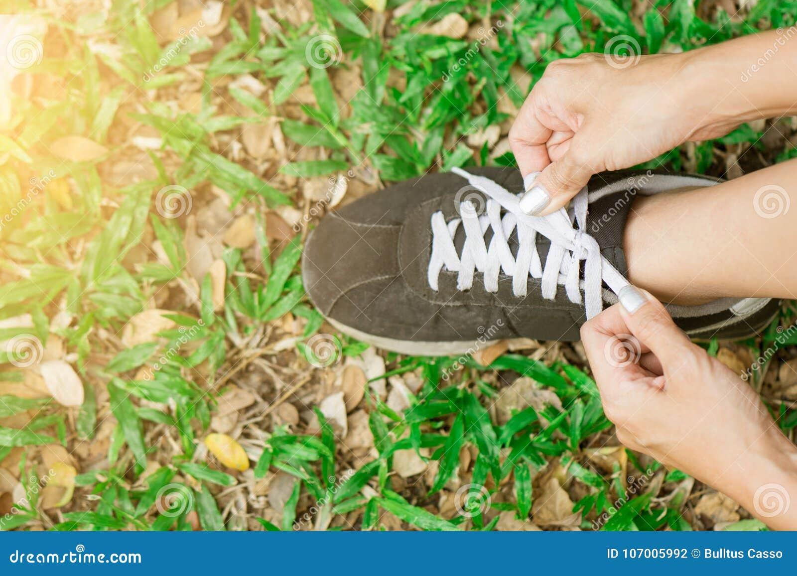 Женщина получая готовый побежать и связывая идущие ботинки