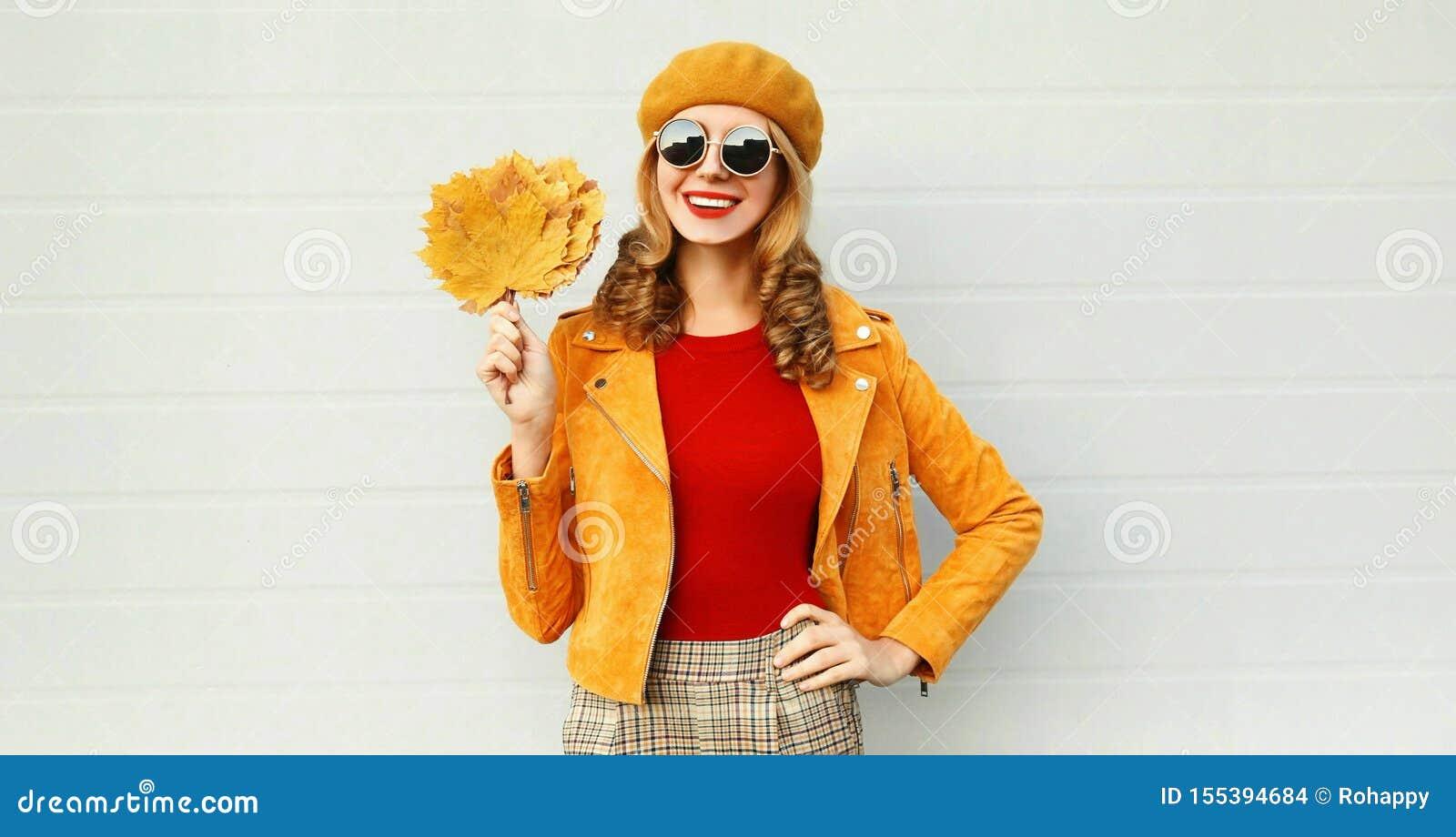 Женщина портрета осени усмехаясь держа желтые кленовые листы нося французский берет представляя на улице города над серой стеной