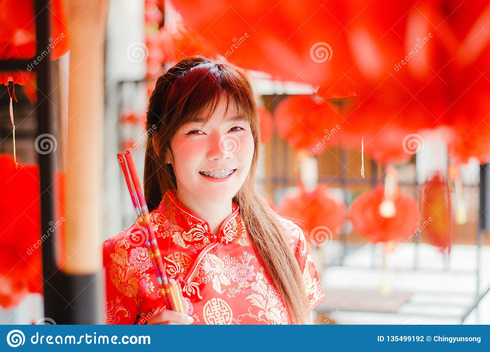 Женщина портрета очаровательная красивая азиатская носит cheongsam для того чтобы одевать для выбора покупки ладан, в китайском Н