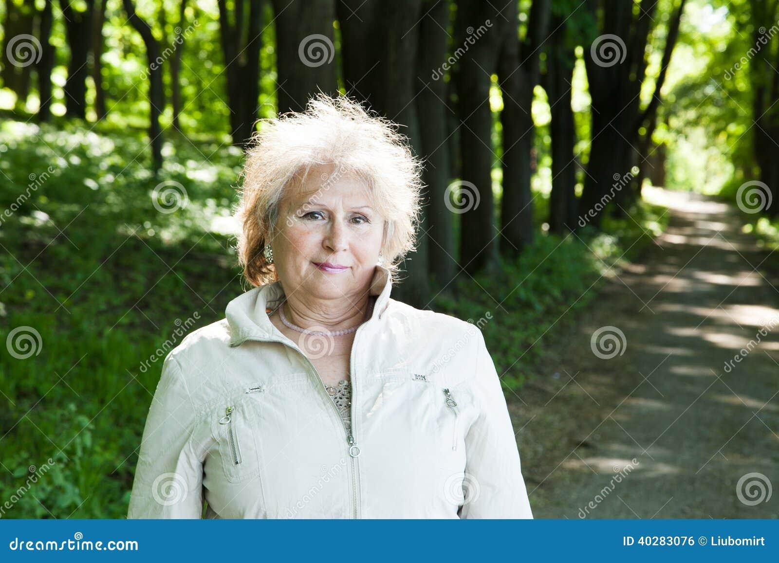 Женщина постаретая старшием outdoors в лесе