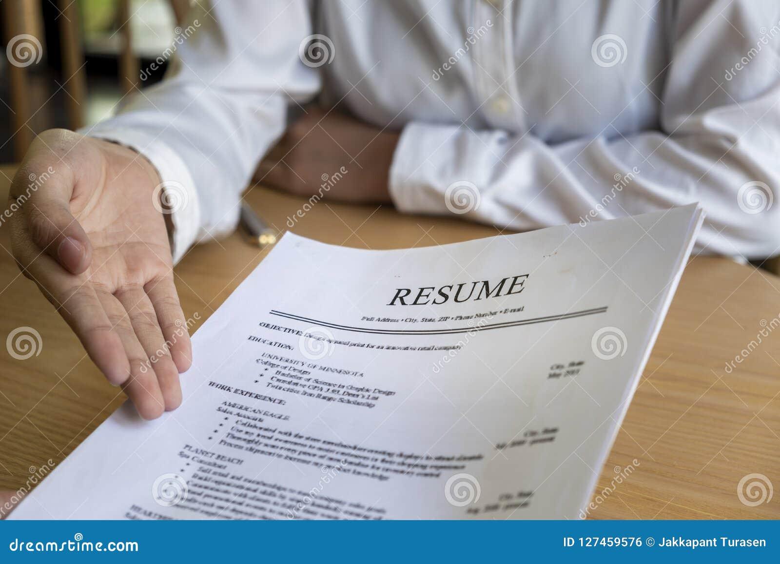 Женщина представляет заявление о приеме на работу, интервьюер читая резюме