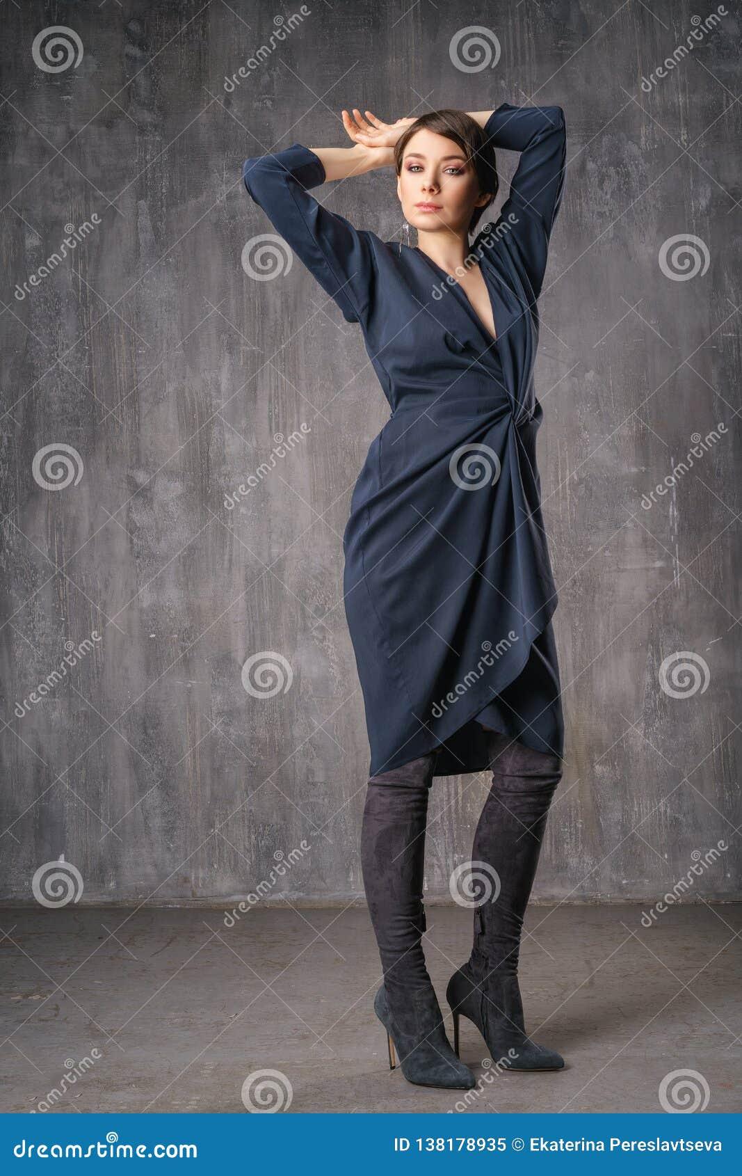 Женщина представляя в модной одежде в студии на заднем плане