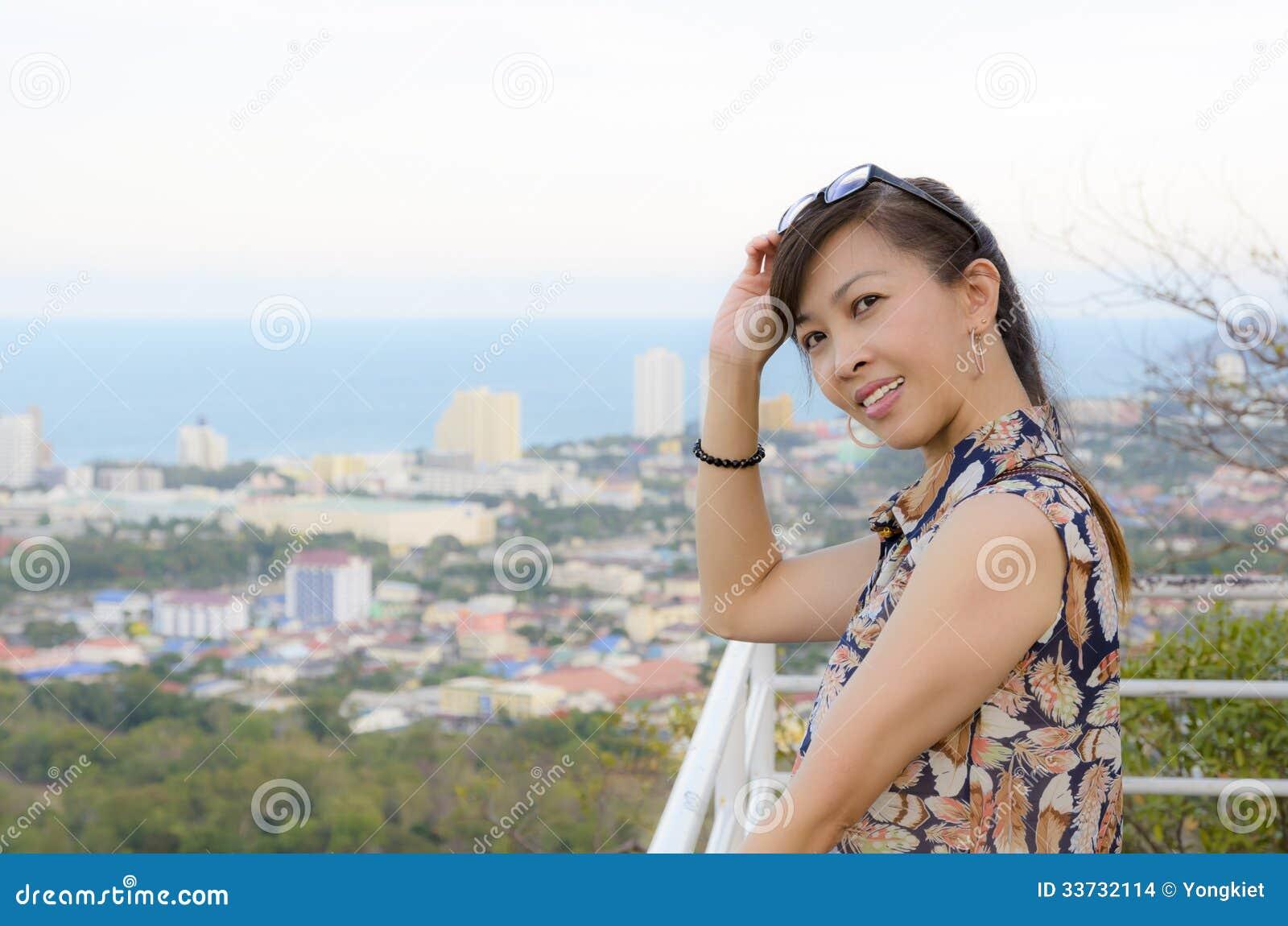 Женщина представляет на высокой точке обозревая город.