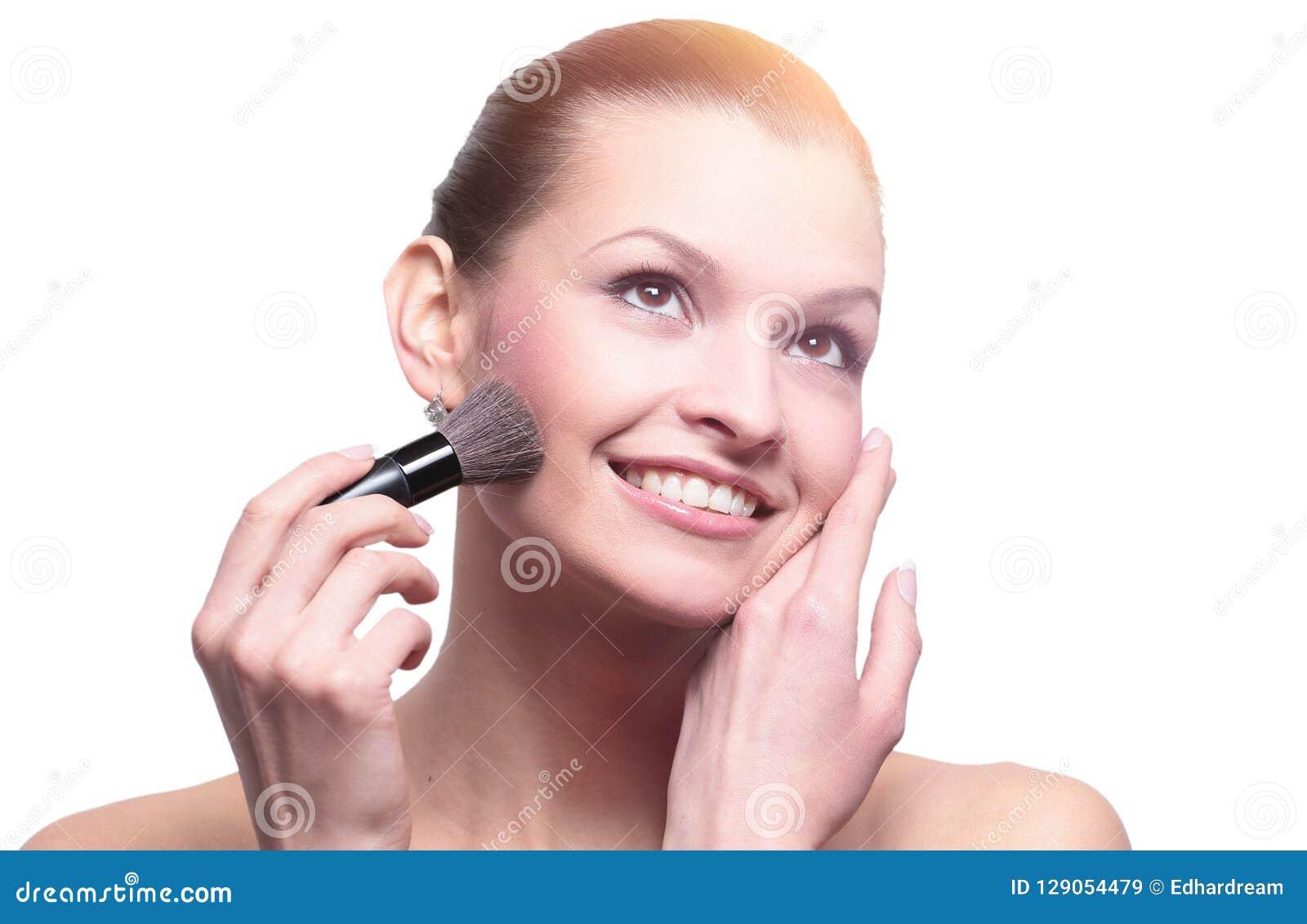 Женщина прикладывая сухое косметическое tonal учреждение на стороне используя m