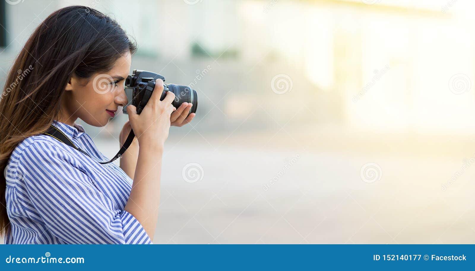 Женщина принимая фото используя профессиональную камеру Молодой фотограф, естественный свет r