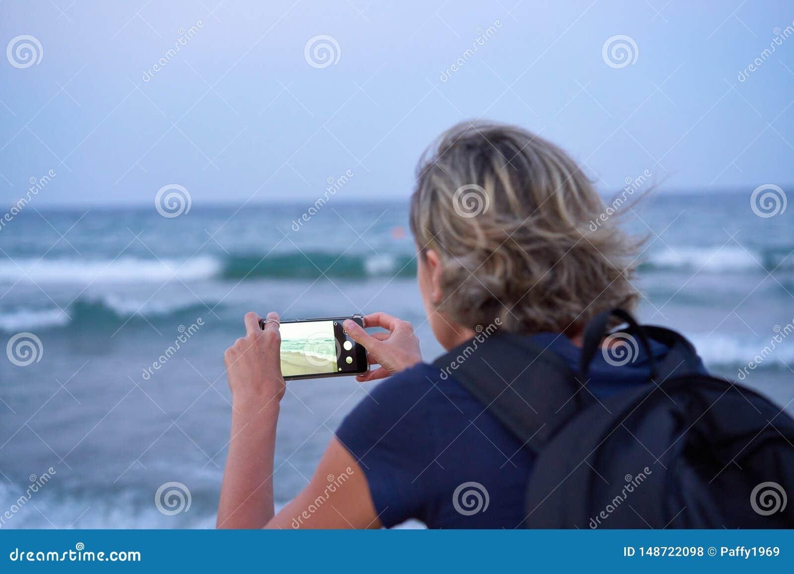 Женщина принимая фото моря по умному телефону на заходе солнца