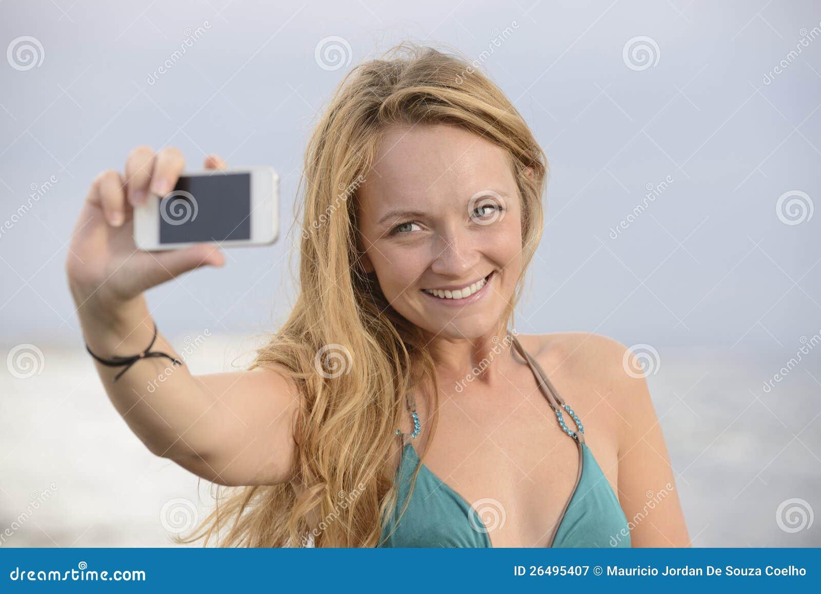 Женщина принимая фото с мобильным телефоном на пляже