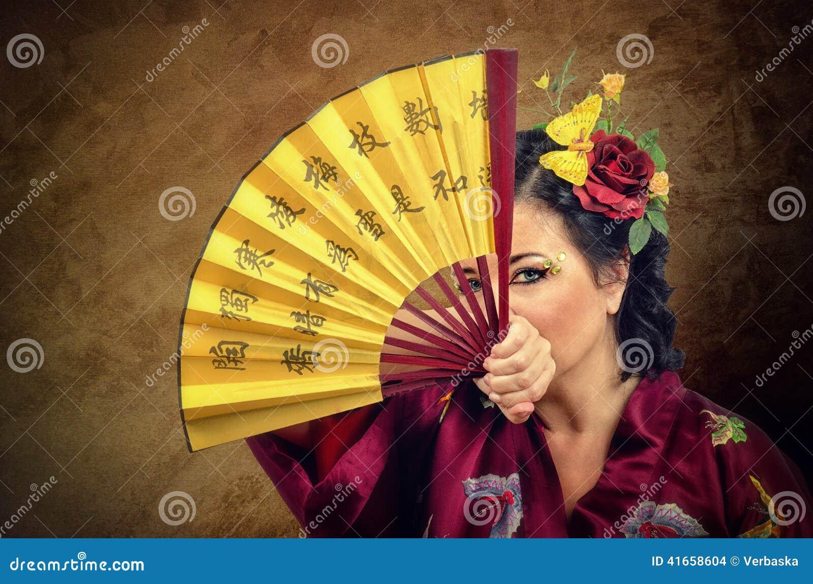 Женщина при волосы цветков смотря вас через азиатский вентилятор