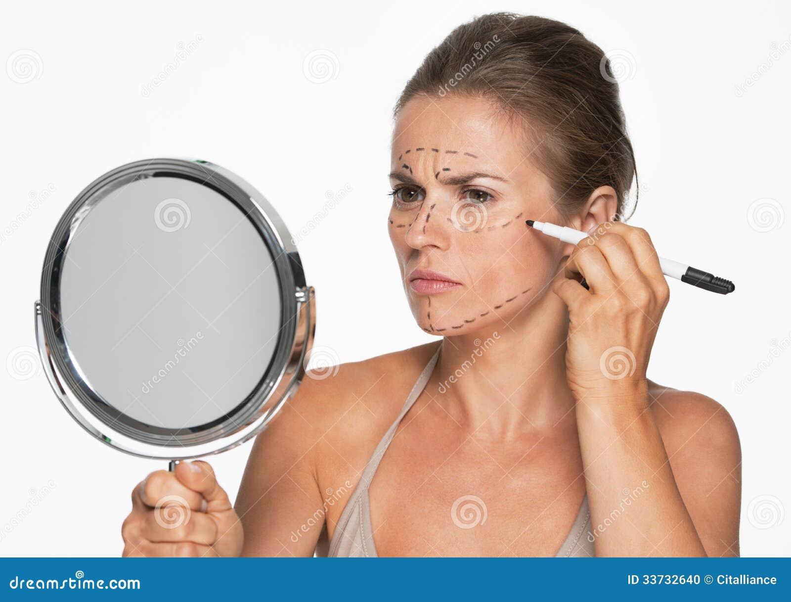 Женщина при зеркало делая метки пластической хирургии на стороне
